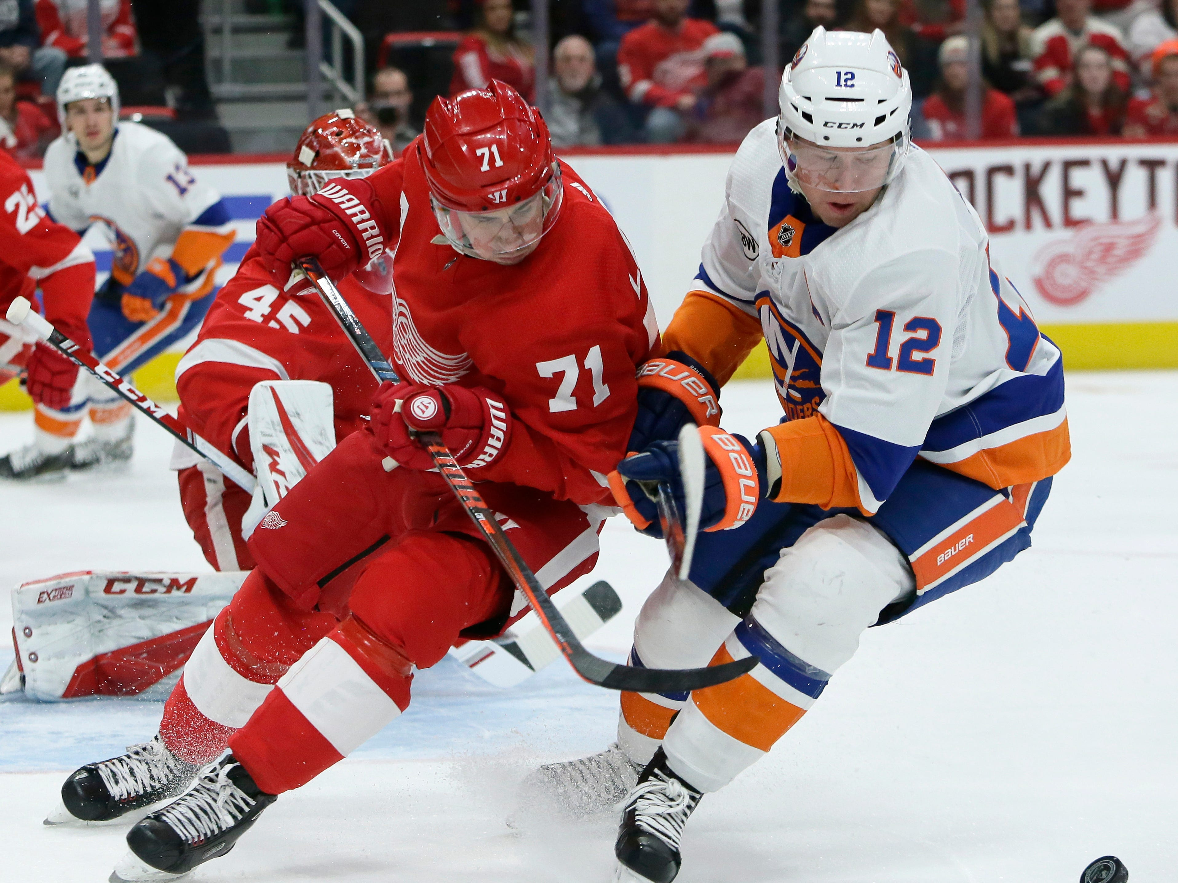 New York Islanders right wing Josh Bailey (12) tries to push Detroit Red Wings center Dylan Larkin (71) off the puck during the first period.