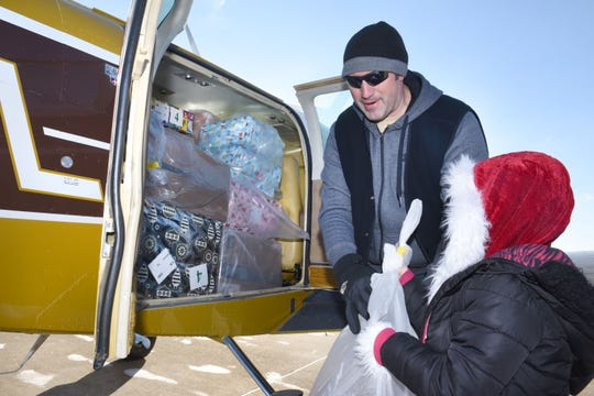 Aaron Sedine gets help from his daughter Trista while loading his plane with Christmas gifts.