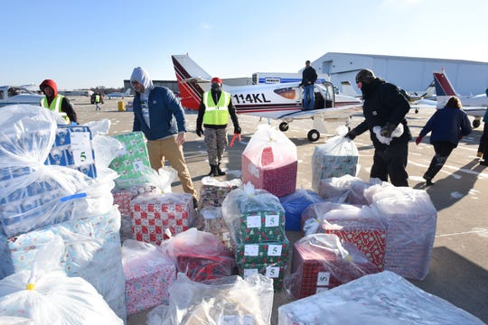 Volunteers with Operation Good Cheer prepare to load airplanes with 20,000 Christmas gifts to be delivered to more than 6,700 children and adults with special needs around Michigan. Volunteers at Oakland County International Airport will load the gifts into about 260 airplanes for delivery to 29 airports around the state.