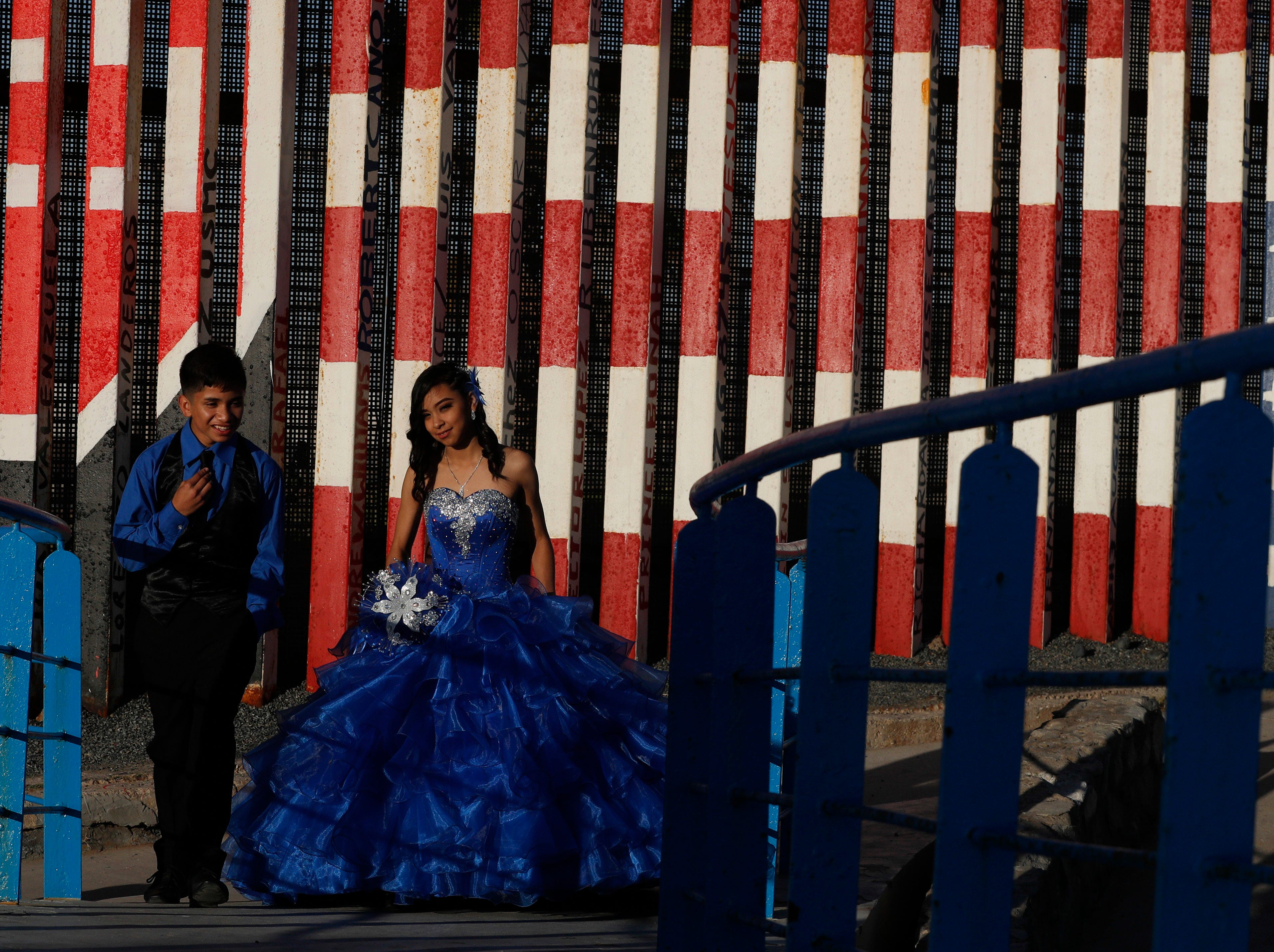 Josalyn Herrera walks in front of a section of the U.S. border wall painted in the colors of the American flag between poses during a photo session for her quinceanera, or 15th birthday celebration, in Tijuana, Mexico, Saturday, Dec. 8, 2018.
