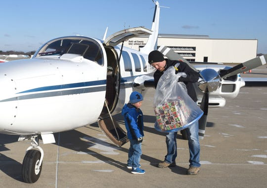 Brad Pugh and his son Weston, 5,  load Christmas gifts into a twin-prop aircraft.