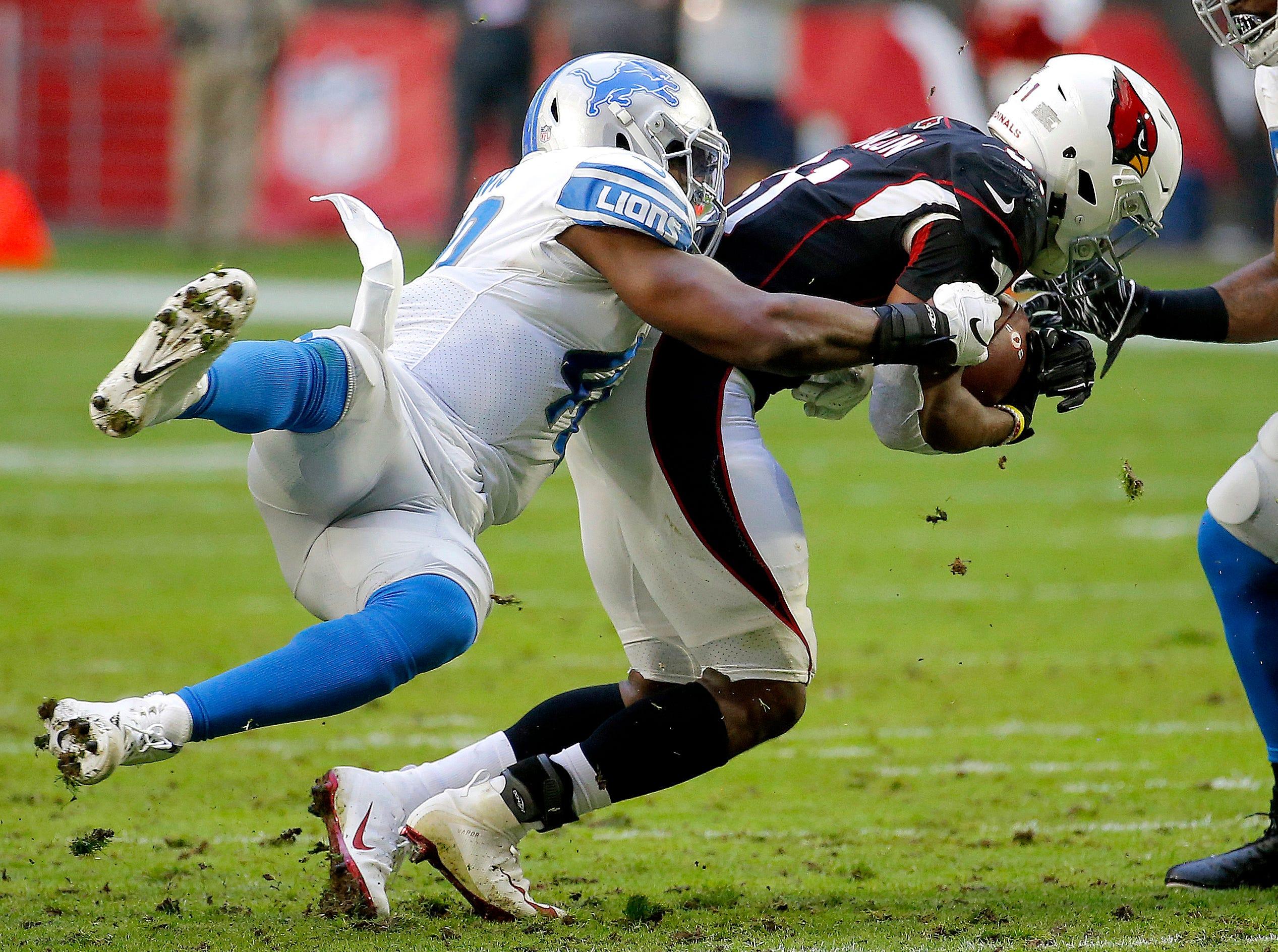 Arizona Cardinals running back David Johnson is hit by Detroit Lions middle linebacker Jarrad Davis, left, during the first half.