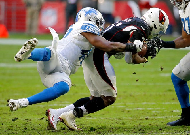 Arizona Cardinals running back David Johnson is hit by Detroit Lions middle linebacker Jarrad Davis, left, during the first half.