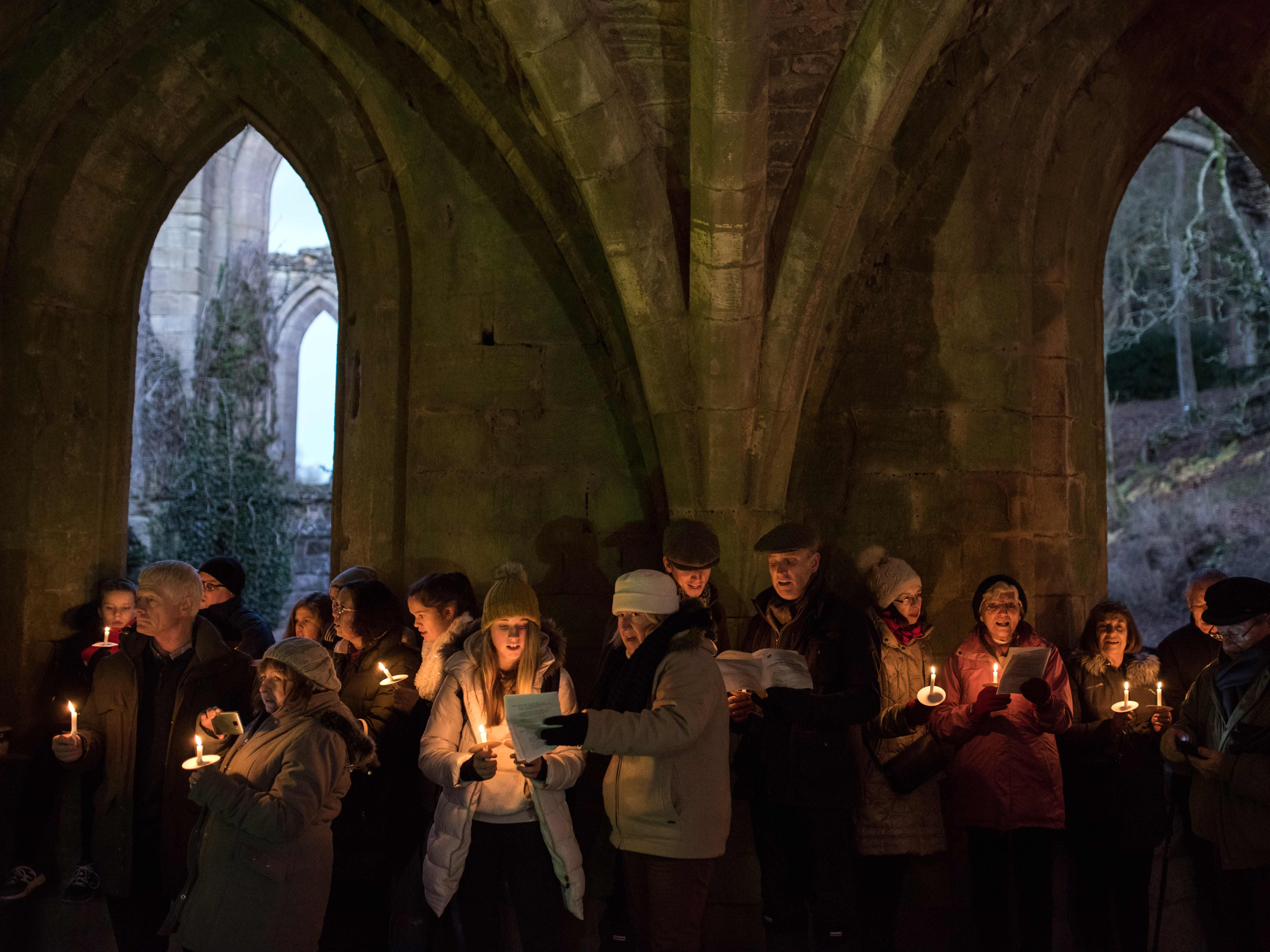 """People attend the annual """"Carols by Candlelight"""" service, which features nearly 1,000 candles, in the cellarium area of the ruins of Fountains Abbey in northern England on December 9, 2018. The abbey, which was founded in 1132 by 13 Benedictine monks, is designated as a UNESCO World Heritage Site and is owned and managed by the National Trust."""