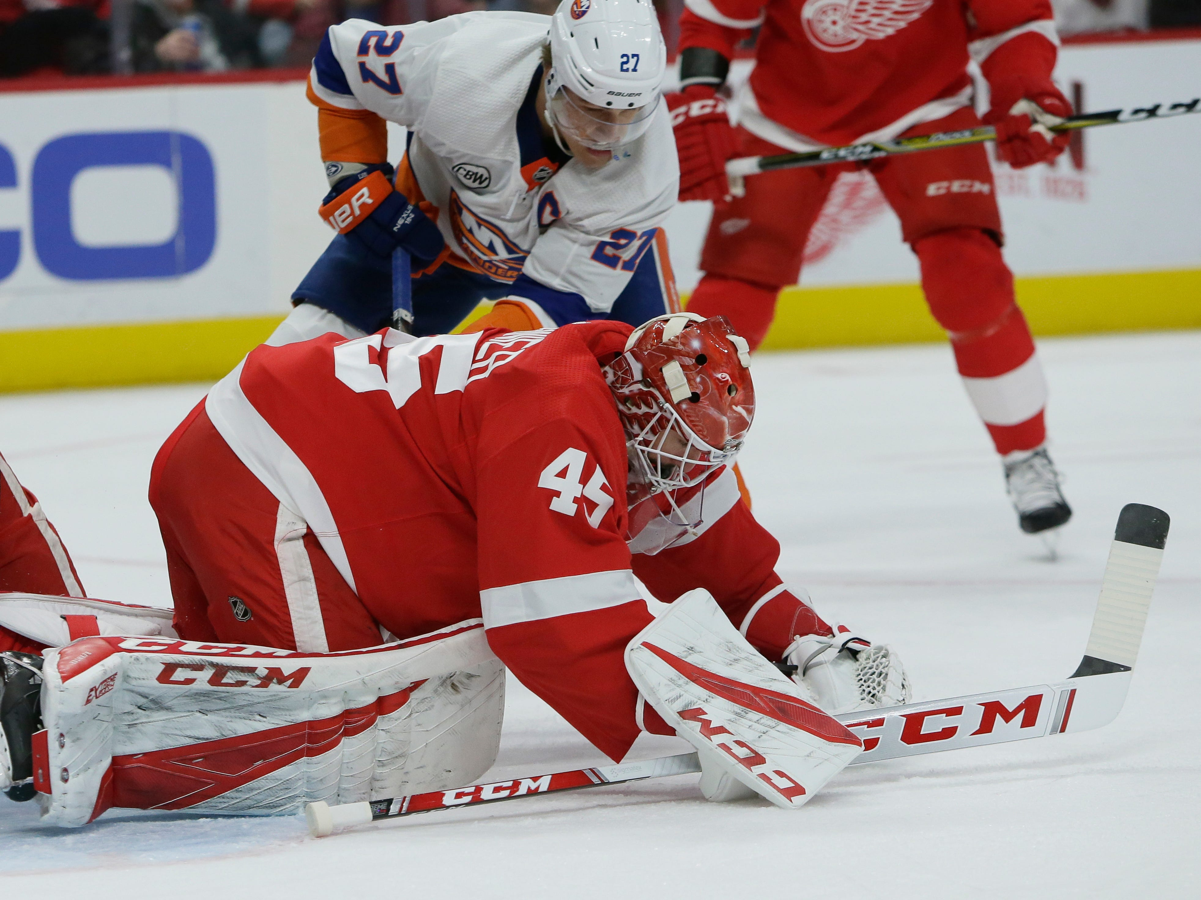 Detroit Red Wings goaltender Jonathan Bernier (45) stops a puck against New York Islanders left wing Anders Lee (27) during the first period.