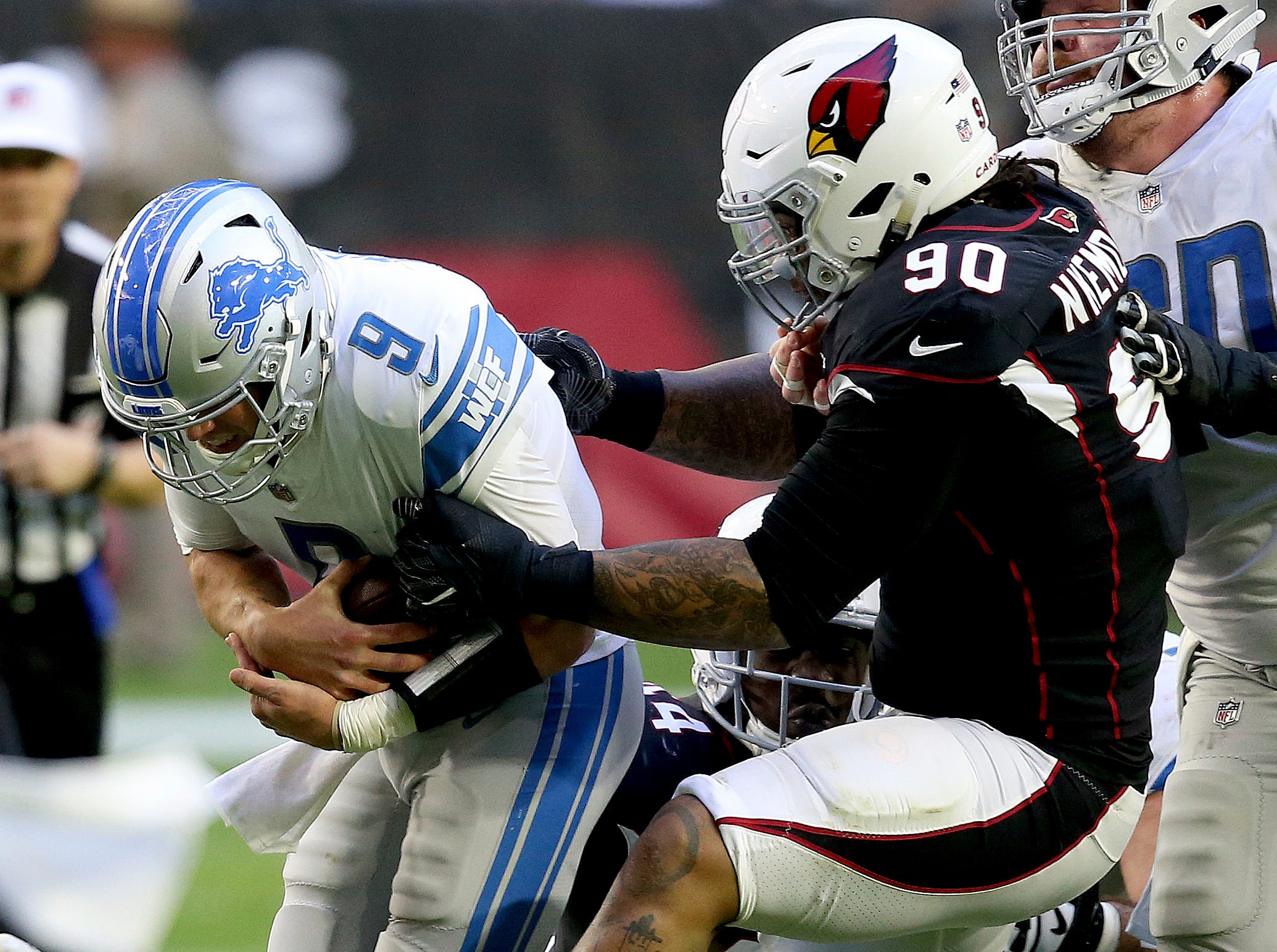 Detroit Lions quarterback Matthew Stafford (9) is hit by Arizona Cardinals defensive tackle Robert Nkemdiche (90) during the first half.