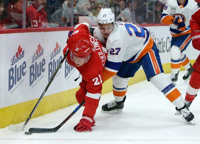 New York Islanders left wing Anders Lee (27) tries to steal the puck from Detroit Red Wings defenseman Dennis Cholowski (21) during the first period of an NHL hockey game Saturday, Dec. 8, 2018, in Detroit. The Islanders won the game, 3-2.
