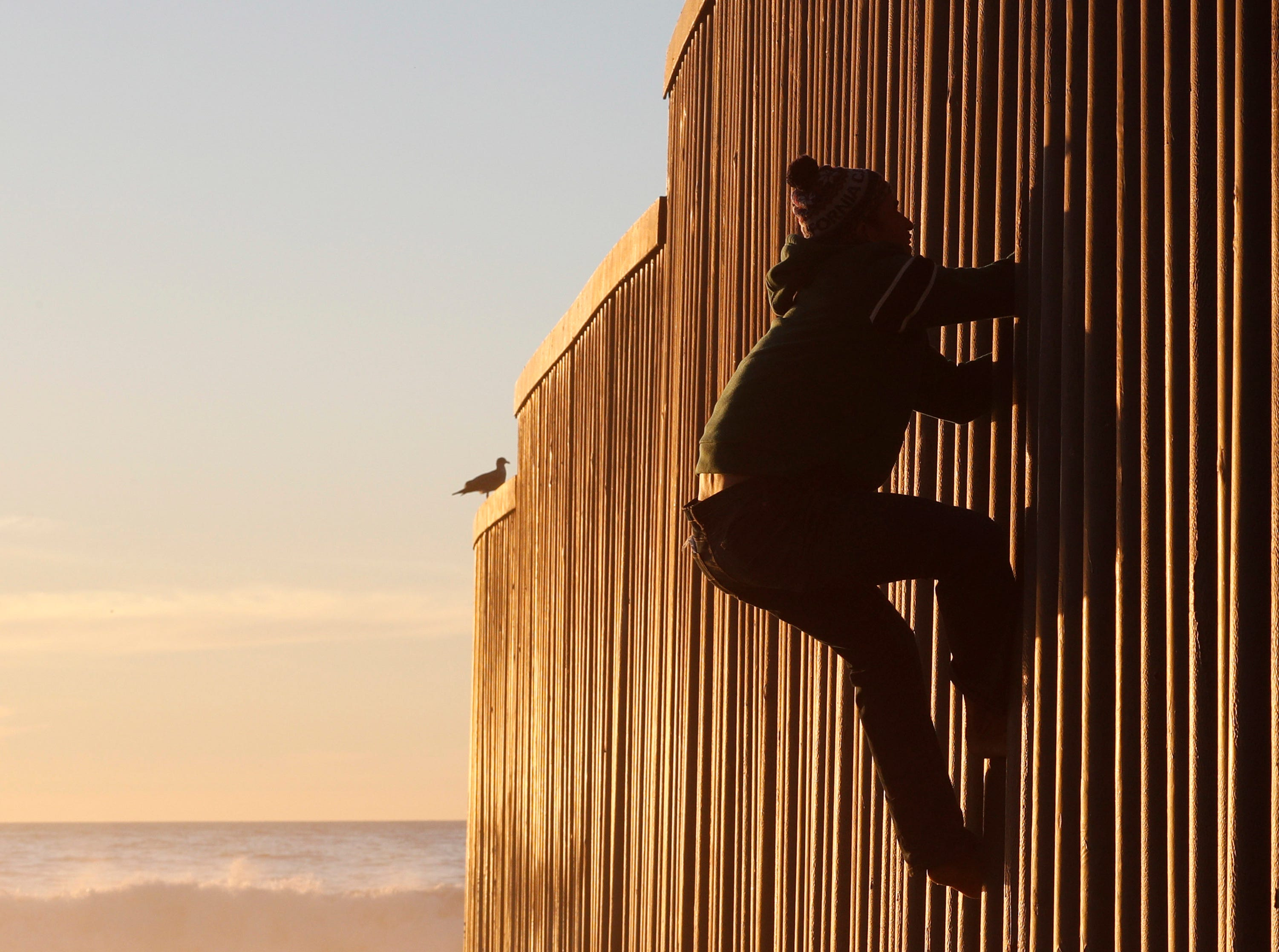 Honduran migrant Jonatan Matamoros Flores, 33, who arrived in October with a migrant caravan, climbs the U.S. border wall to stand atop it before returning to the Mexican side in Tijuana, Mexico, Saturday, Dec. 8, 2018. U.S. inspectors at the main border crossing in San Diego are processing up to about 100 asylum claims day, leaving thousands of migrants waiting in Tijuana, while some are avoiding the wait by crossing illegally to turn themselves in.