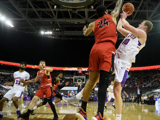 University of Evansville's Evan Kuhlman (10) passes the ball as Ball State's Trey Moses (24) blocks him from making a shot during the first half at Ford Center in Evansville, Ind., Sunday, Dec. 9, 2018. The Purple Aces defeated the Cardinals 89-77.