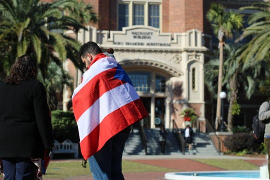 Kristian Diaz, programming director of HLSU, stands with a flag over his shoulders at the end of the march.