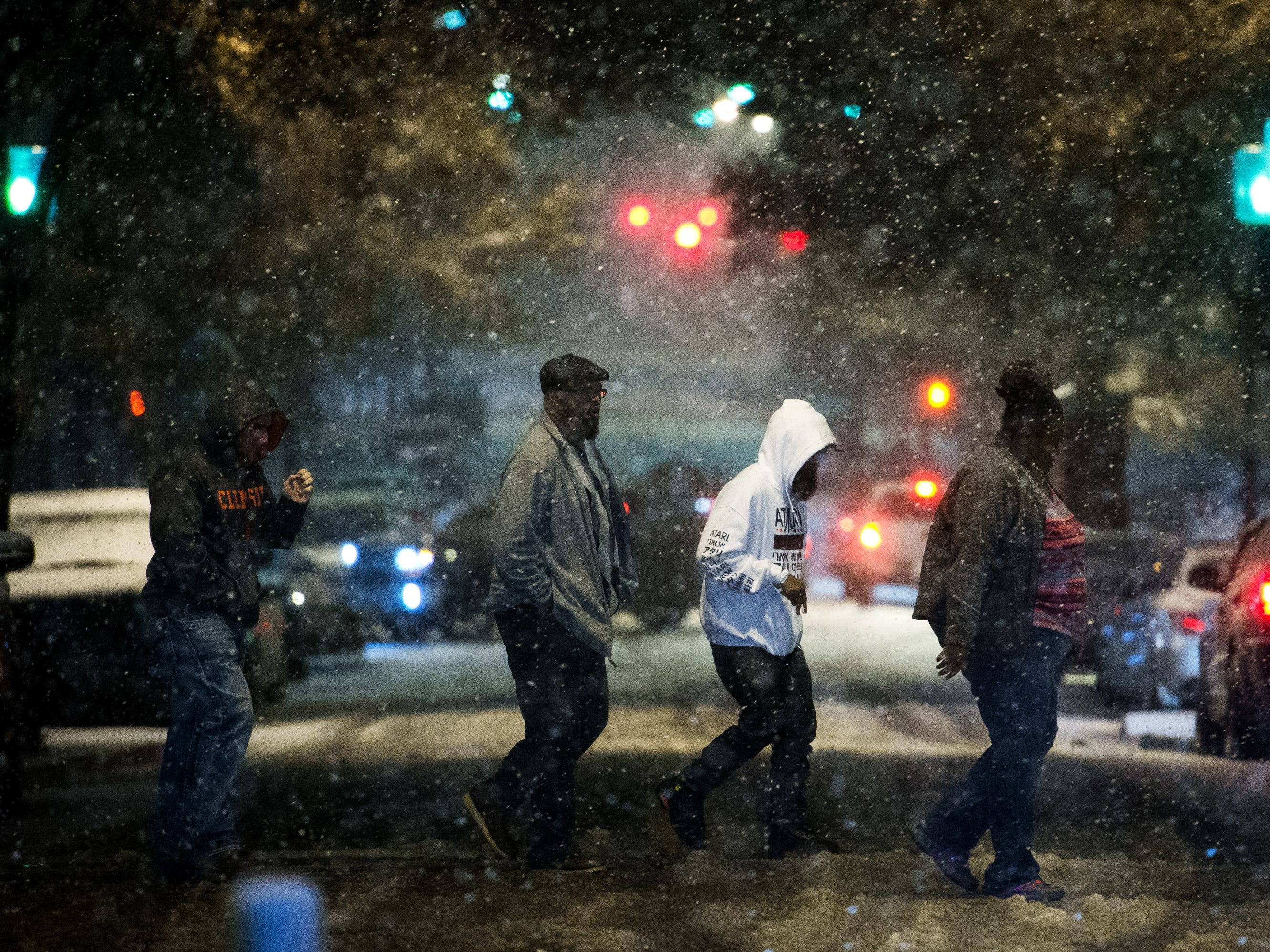 People walk across the street as it begins to snow in downtown Greenville on Sunday, Dec. 9, 2018.