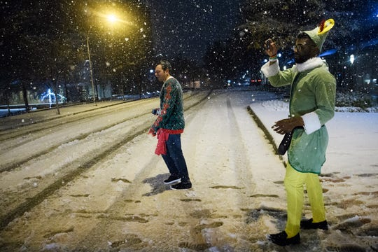 Trey Black, right, takes photos of the snow on his smartphone as he and Austin Hurst walk down Main Street on Sunday, Dec. 9, 2018.