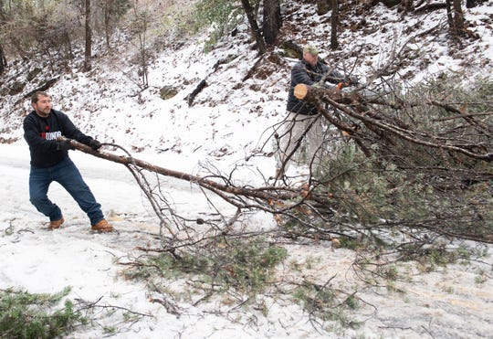From left, Aaron Chapman and Dave Williams work to clear a downed tree blocking traffic on Farrs Bridge Road Sunday, Dec. 09, 2018.