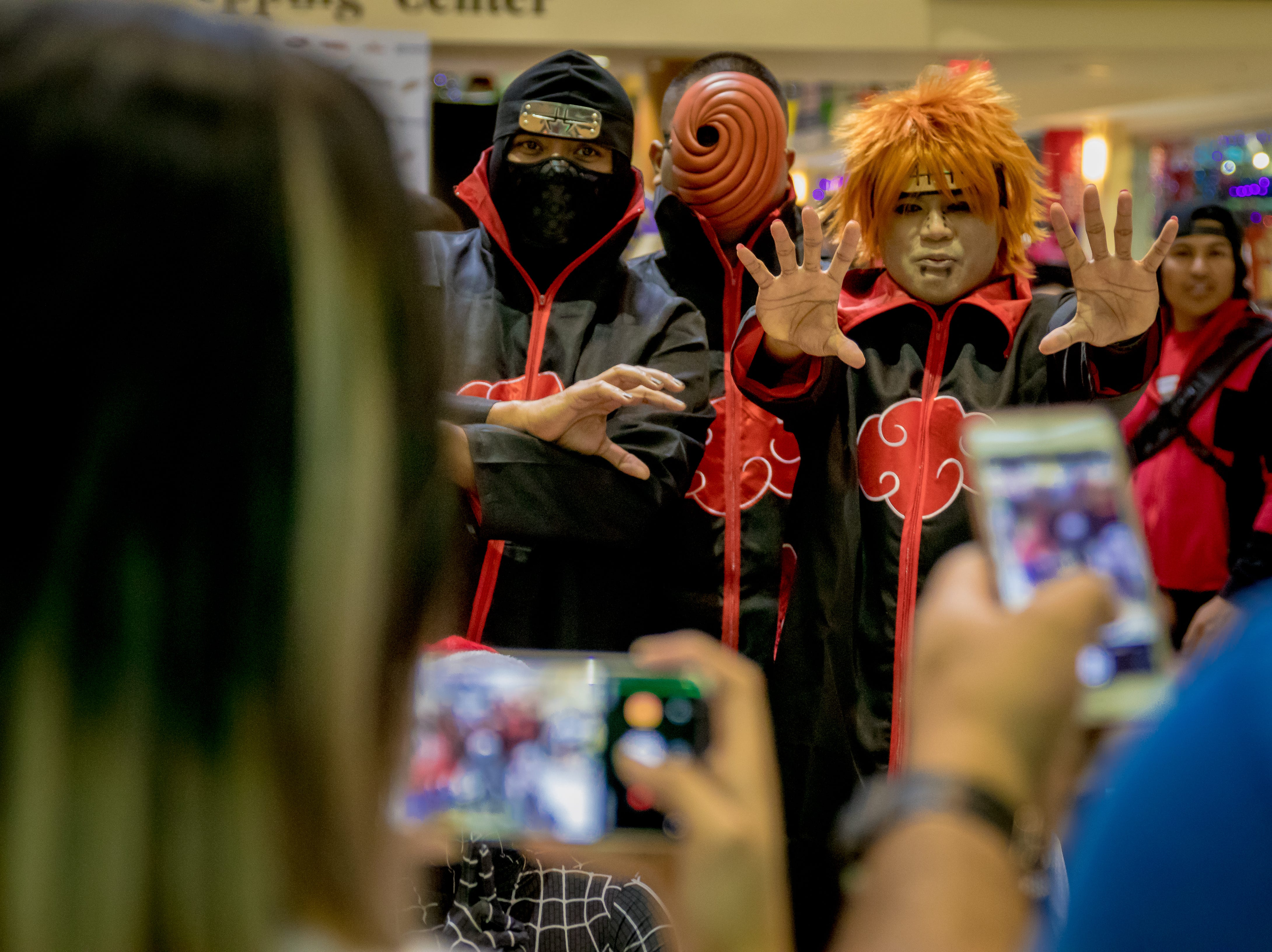 Attendees take photos of cosplayers during the Herocon event held at Agana Shopping Center on Dec. 9.