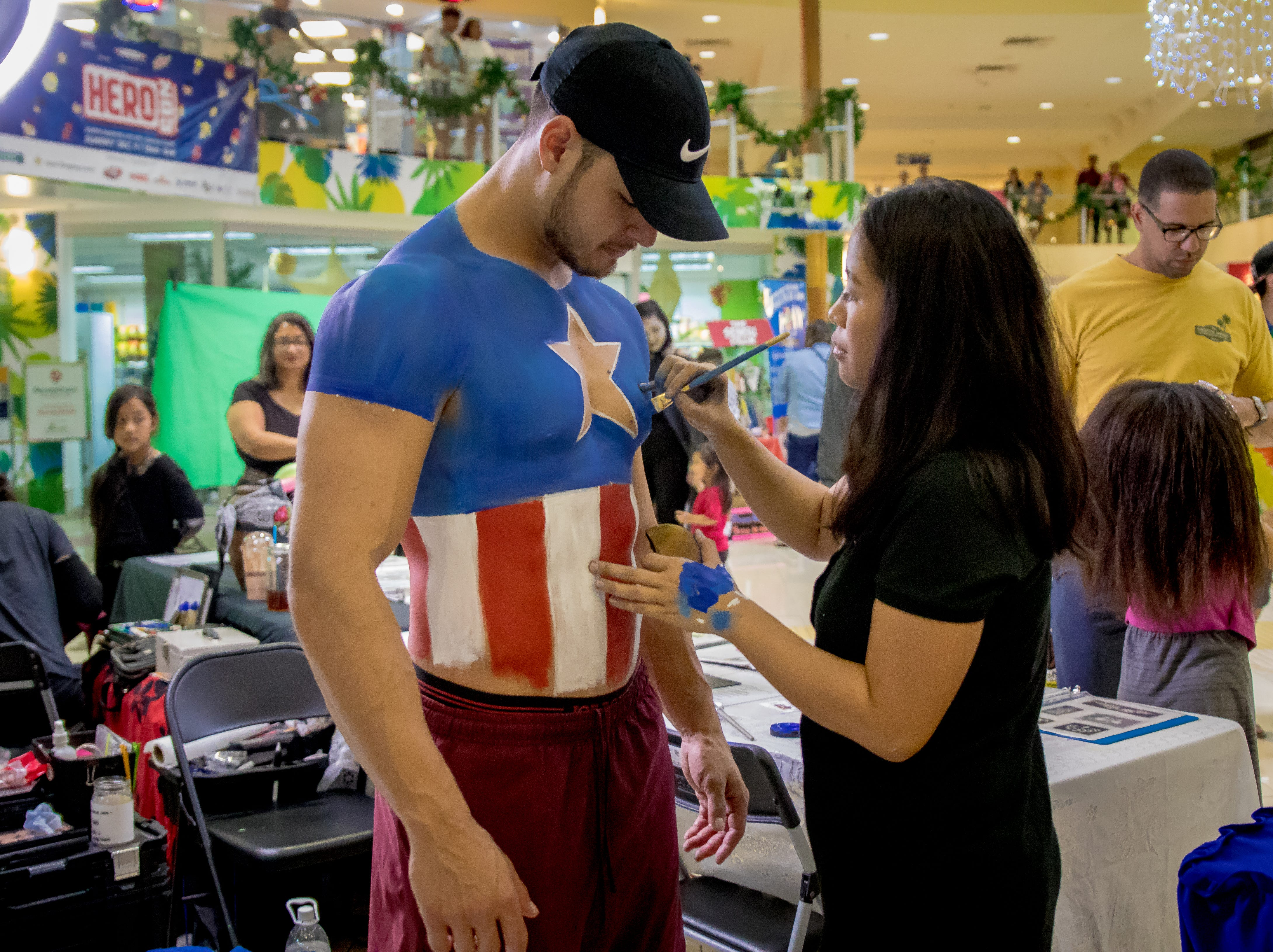 Jonathan Muth gets his body painted as Captain America by Julie Ann Donato of Muse Face and Body Art during the Herocon event held at Agana Shopping Center on Dec. 9.
