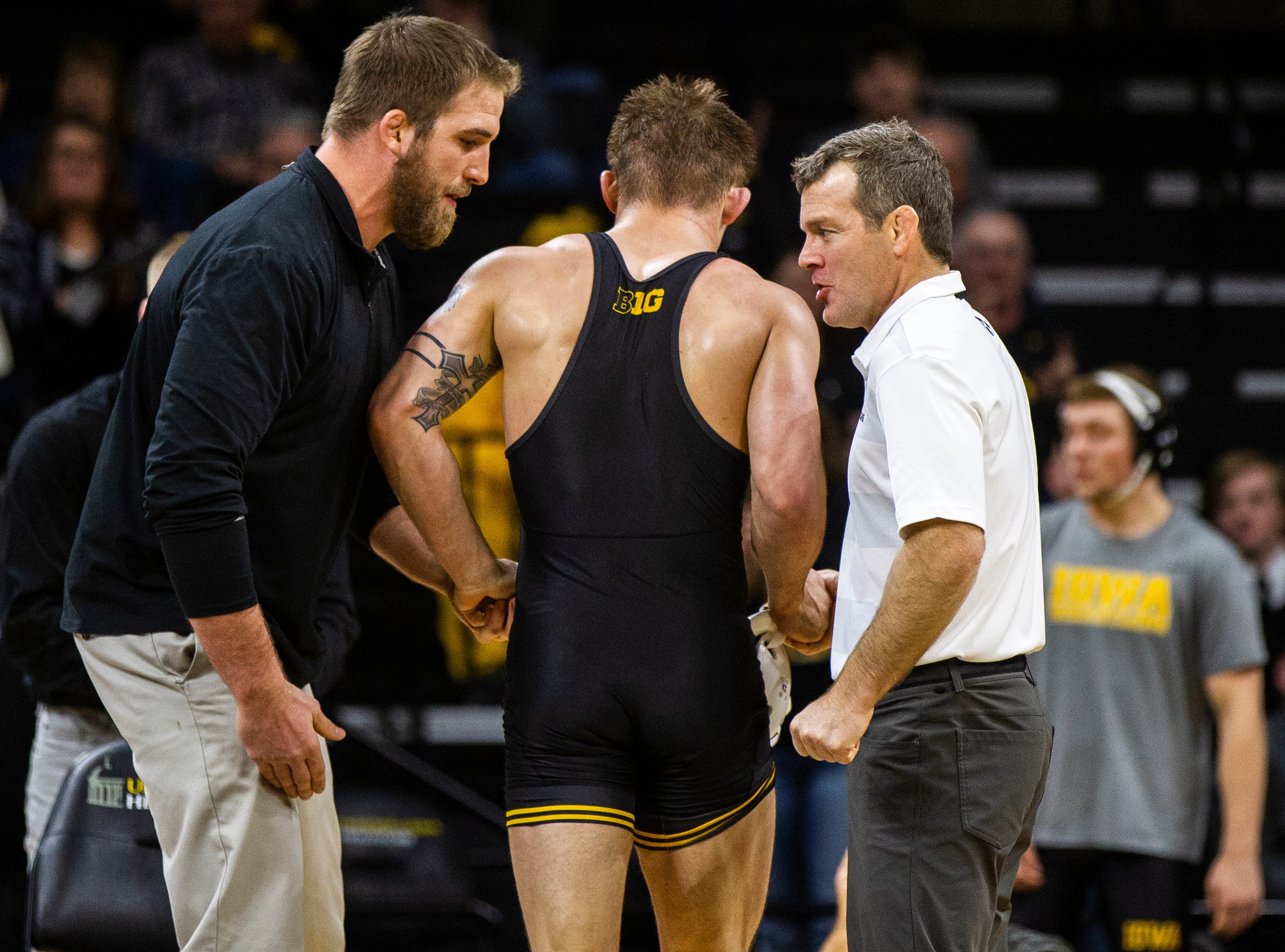 Iowa volunteer assistant coach Bobby Telford (left) and head coach Tom Brands congratulate Cash Wilcke after he scored a decision over Lehigh at 184 during a NCAA wrestling dual on Saturday, Dec. 8, 2018, at Carver-Hawkeye Arena in Iowa City.