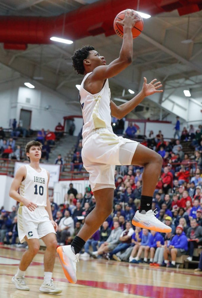 Cathedral High School's guard Tayshawn Comer (12) heads to the hoop for a basket during a Tip Off Classic game between Cathedral High School and Zionsville Community High School, held at the Southport Fieldhouse, on Saturday, Dec. 8, 2018. Left, Cathedral High School's Justin Hensley (10).