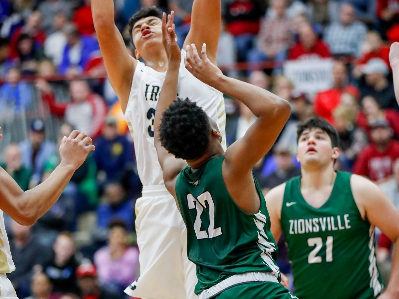 Cathedral High School's forward Isaac Farah (34), Zionsville Community High School's Anthony Scales (22), and teammate Brandon Vernon (21) reach for a rebound during a Tip Off Classic game between Cathedral High School and Zionsville Community High School, held at the Southport Fieldhouse, on Saturday, Dec. 8, 2018.