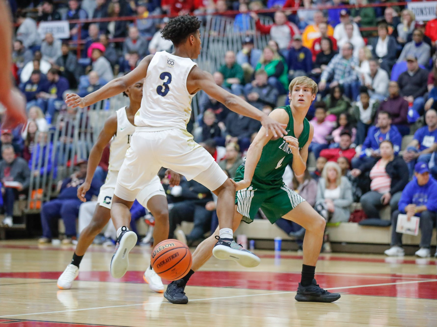 Zionsville Community High School's guard Ben Weidner (4) passes the ball around Cathedral high School's Grant Taueg (3) and Tayshawn Comer (12), during a Tip Off Classic game between Cathedral High School and Zionsville Community High School, held at the Southport Fieldhouse, on Saturday, Dec. 8, 2018.