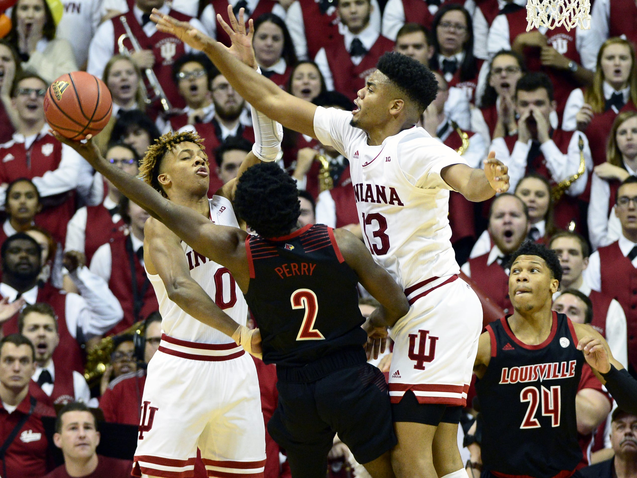 Indiana Hoosiers guard Romeo Langford (0) and Indiana Hoosiers forward Juwan Morgan (13) contest a shot from Louisville Cardinals guard Darius Perry (2) during the game against Louisville at Simon Skjodt Assembly Hall in Bloomington, Ind.