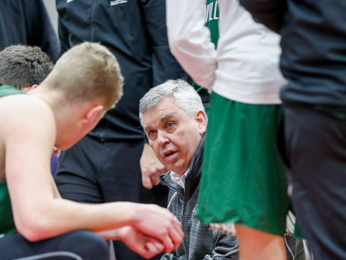 Zionsville Community High School's Head Coach Shaun Busick huddles with players during a time out at the Tip Off Classic game between Cathedral High School and Zionsville Community High School, held at the Southport Fieldhouse, on Saturday, Dec. 8, 2018.