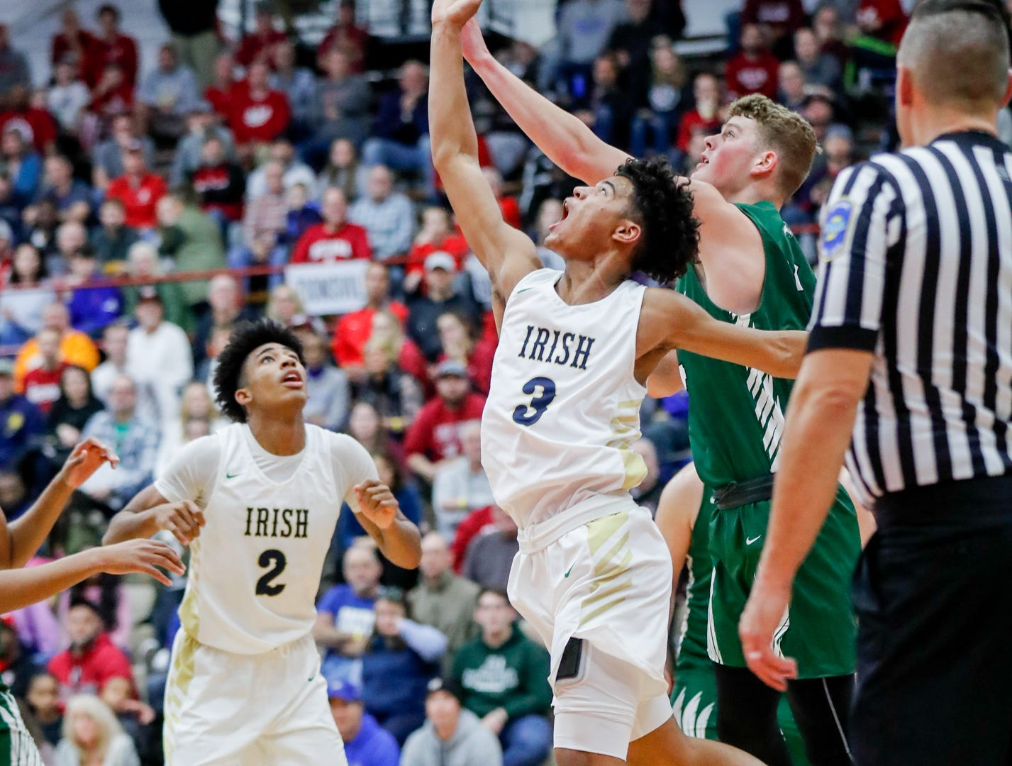 Cathedral high School's Grant Taueg (3), Armaan Franklin (2), and Zionsville Community High School's Gunnar Vannatta (44) reach for a rebound during a Tip Off Classic game between Cathedral High School and Zionsville Community High School, held at the Southport Fieldhouse, on Saturday, Dec. 8, 2018.