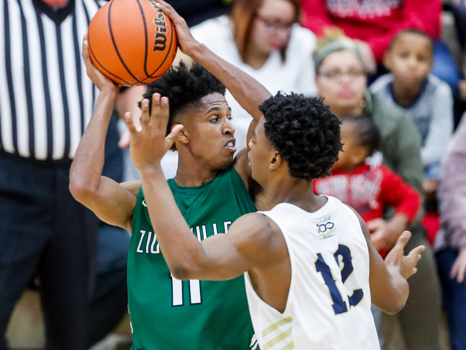 Cathedral High School's guard Tayshawn Comer (12) guards Zionsville Community High School's Isaiah Thompson (11), during a Tip Off Classic game between Cathedral High School and Zionsville Community High School, held at the Southport Fieldhouse, on Saturday, Dec. 8, 2018.