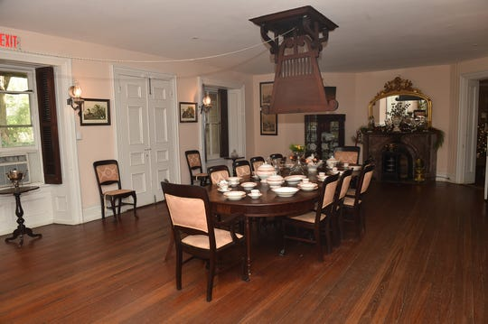 The dining room in Longwood is furnished with period furniture and includes a ceiling fan that is operated by pulling a rope.