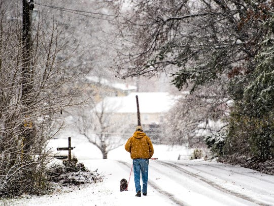 A man walks his dog down a snow-covered Sunflower Road in Knoxville on Dec. 9.