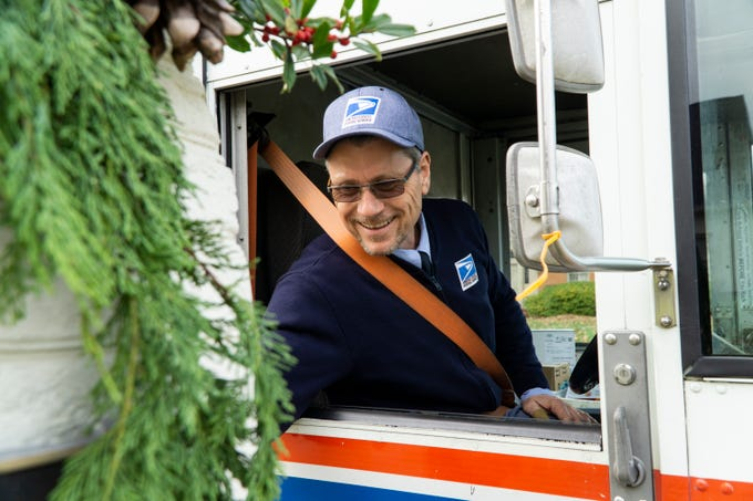 USPS mail carrier Bryan Lay delivers mail to a home in West Knoxville on Friday, Dec. 7. USPS expects to handle 16 billion pieces of mail this holiday season.