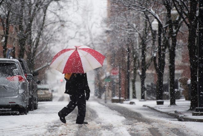 A pedestrian walks as snow falls in downtown Knoxville Sunday Dec. 9, 2018.