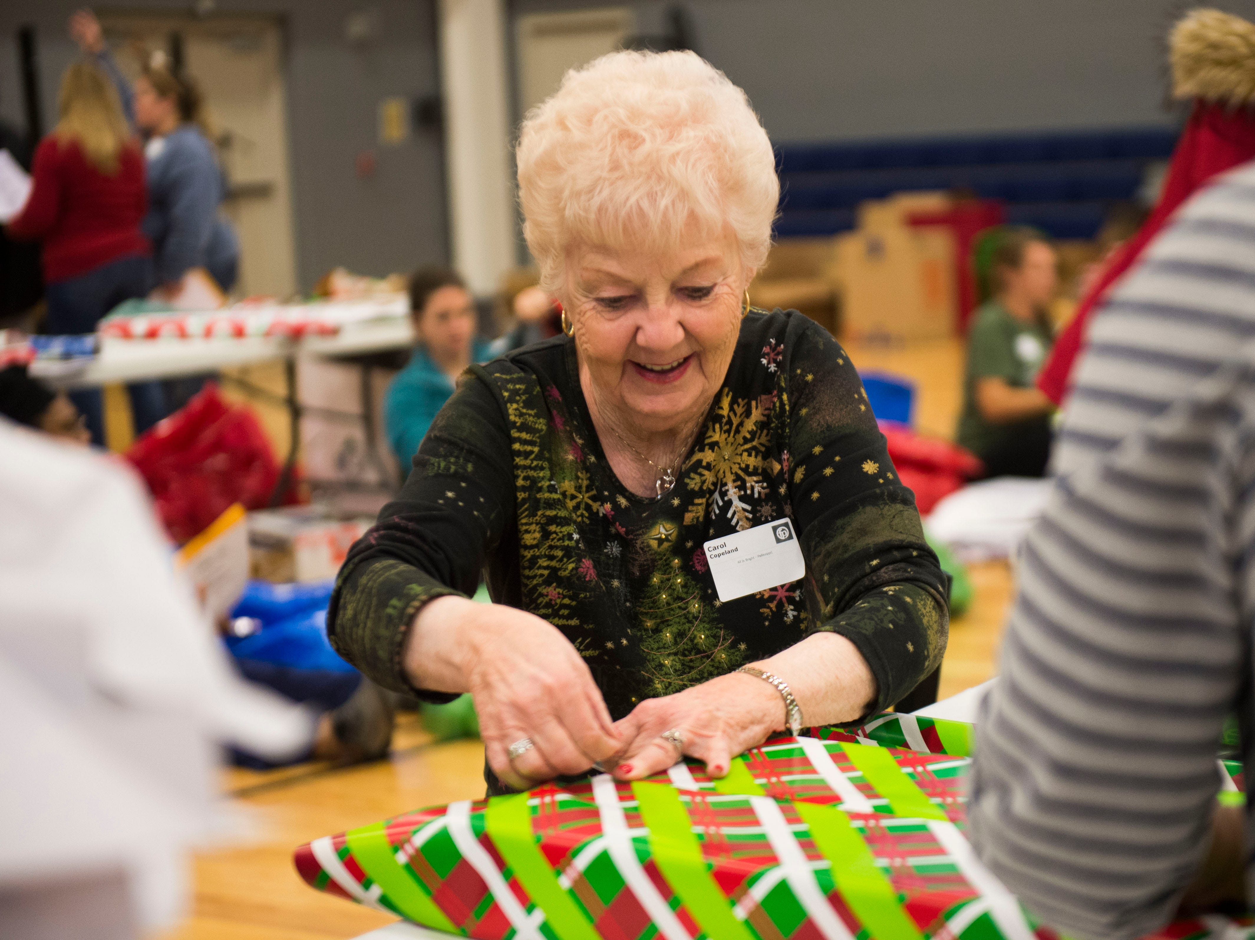 Carol Copeland, of Knoxville wraps gifts at the Boys and Girls Clubs Regal Teen Center in Knoxville Saturday, Dec. 8, 2018. Parents, grandparents or guardians of over 1,500 underserved children were able to pick out a limited number of free gifts for their child.