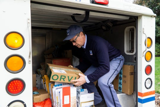FILE: Bryan Lay grabs a package from his mail truck while on his delivery route Dec. 7, 2018.