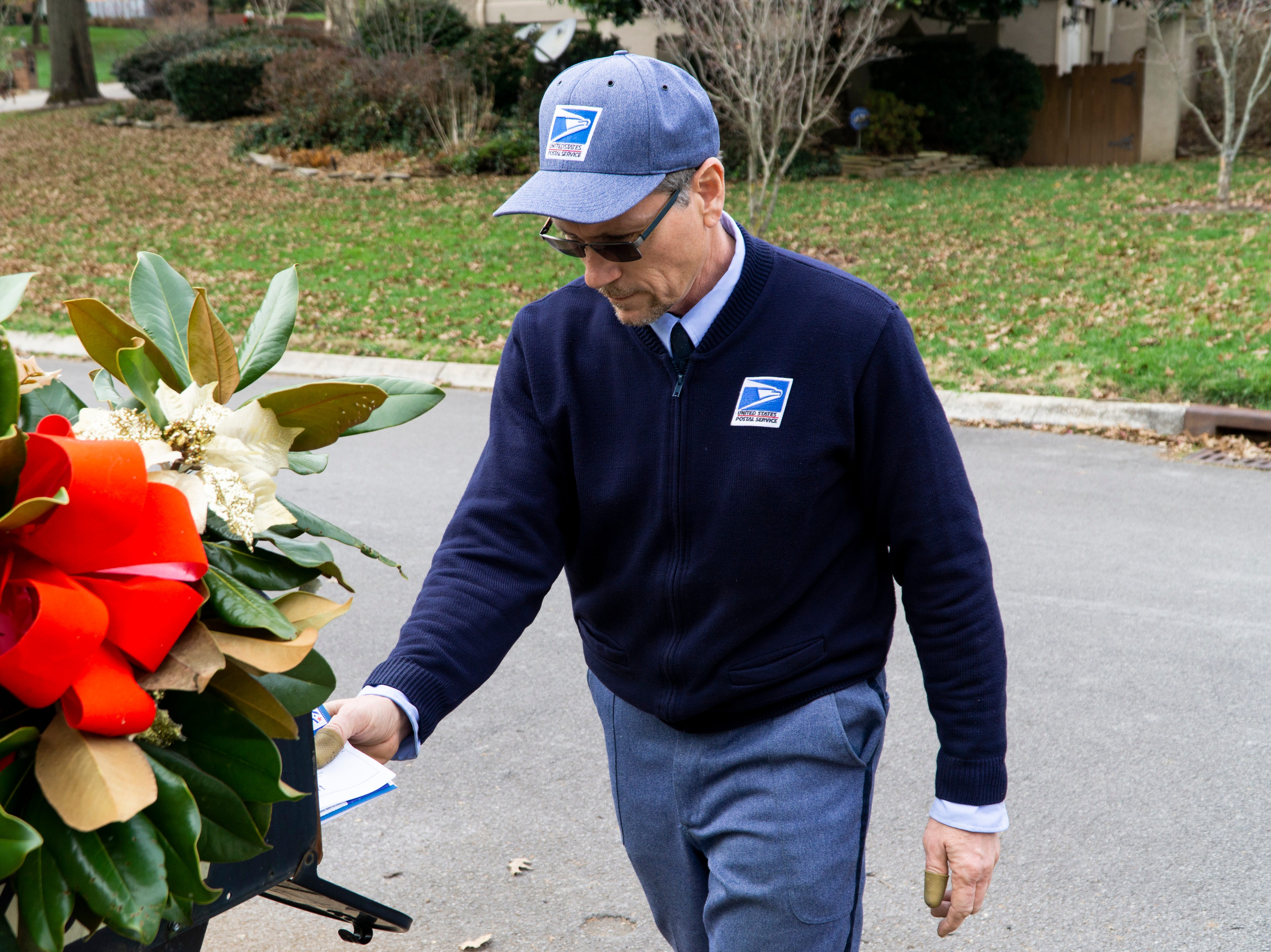 Bryan Lay places delivers a handful of mail to a West Knoxville home on Friday, Dec. 7. USPS is predicting that Monday, Dec. 17, will be the busiest day for shipping this holiday season.