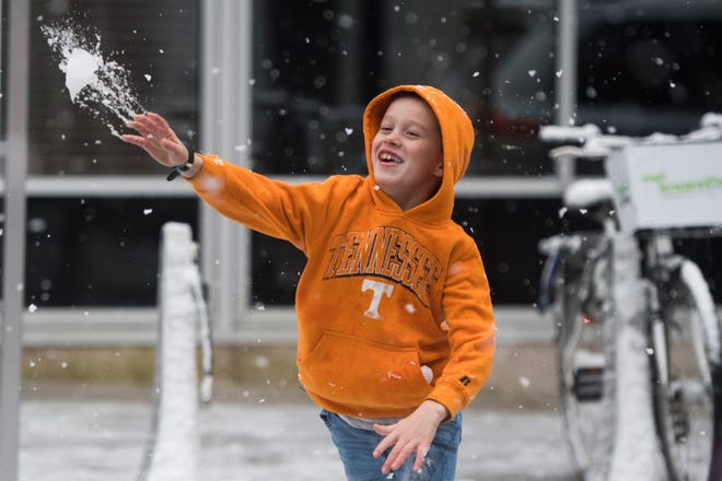 Elijah Eveland, 9, of Knoxville throws a snowball aimed at his dad in downtown Knoxville Sunday Dec. 9, 2018.