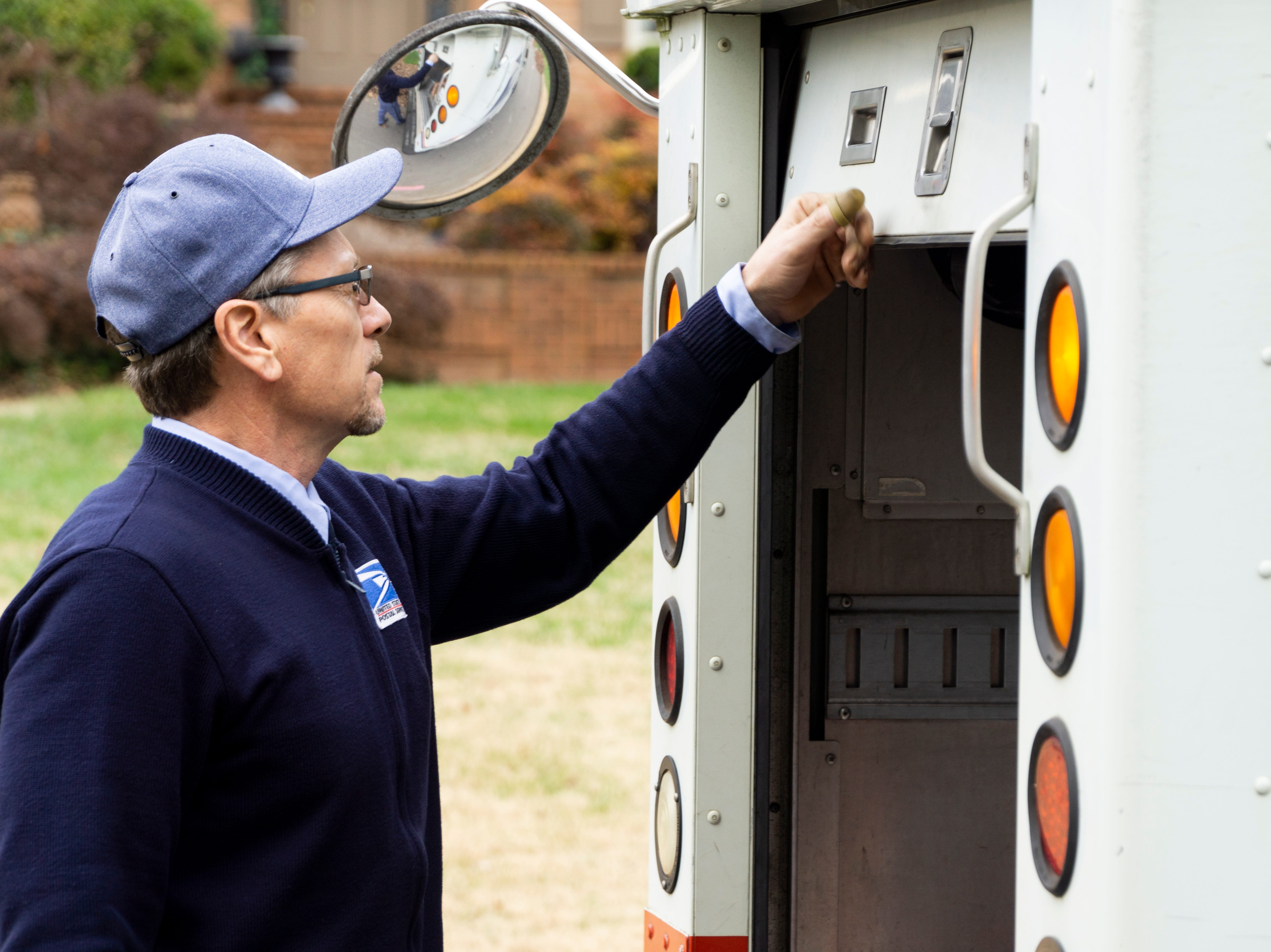 Bryan Lay shuts the door of his mail truck while delivering packages in West Knoxville. Lay has been delivering mail in Knoxville for more than 20 years.