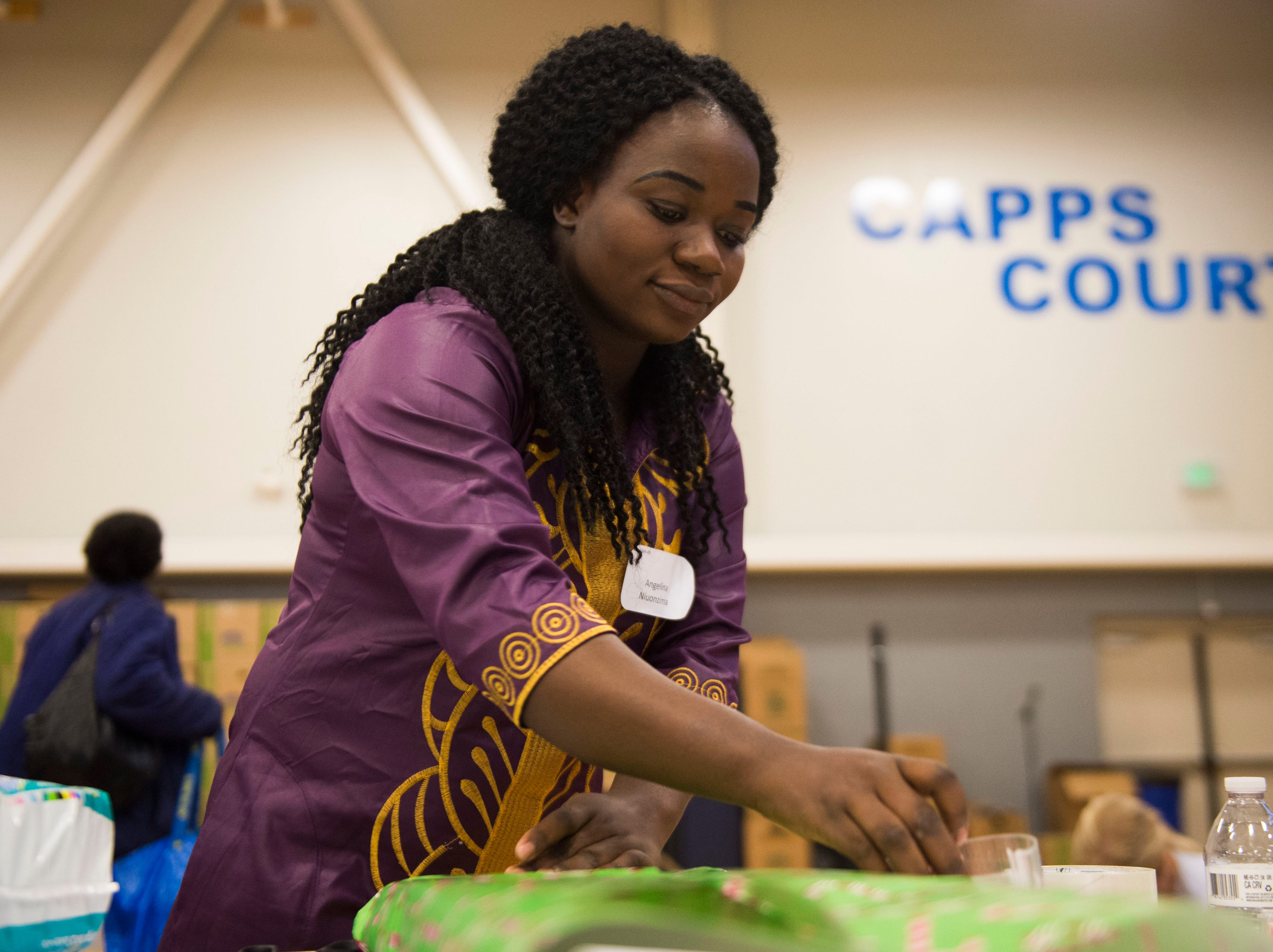 Angelina Niuonzima wraps gifts at the Boys and Girls Clubs Regal Teen Center in Knoxville Saturday, Dec. 8, 2018. Parents, grandparents or guardians of over 1,500 underserved children were able to pick out a limited number of free gifts for their child.