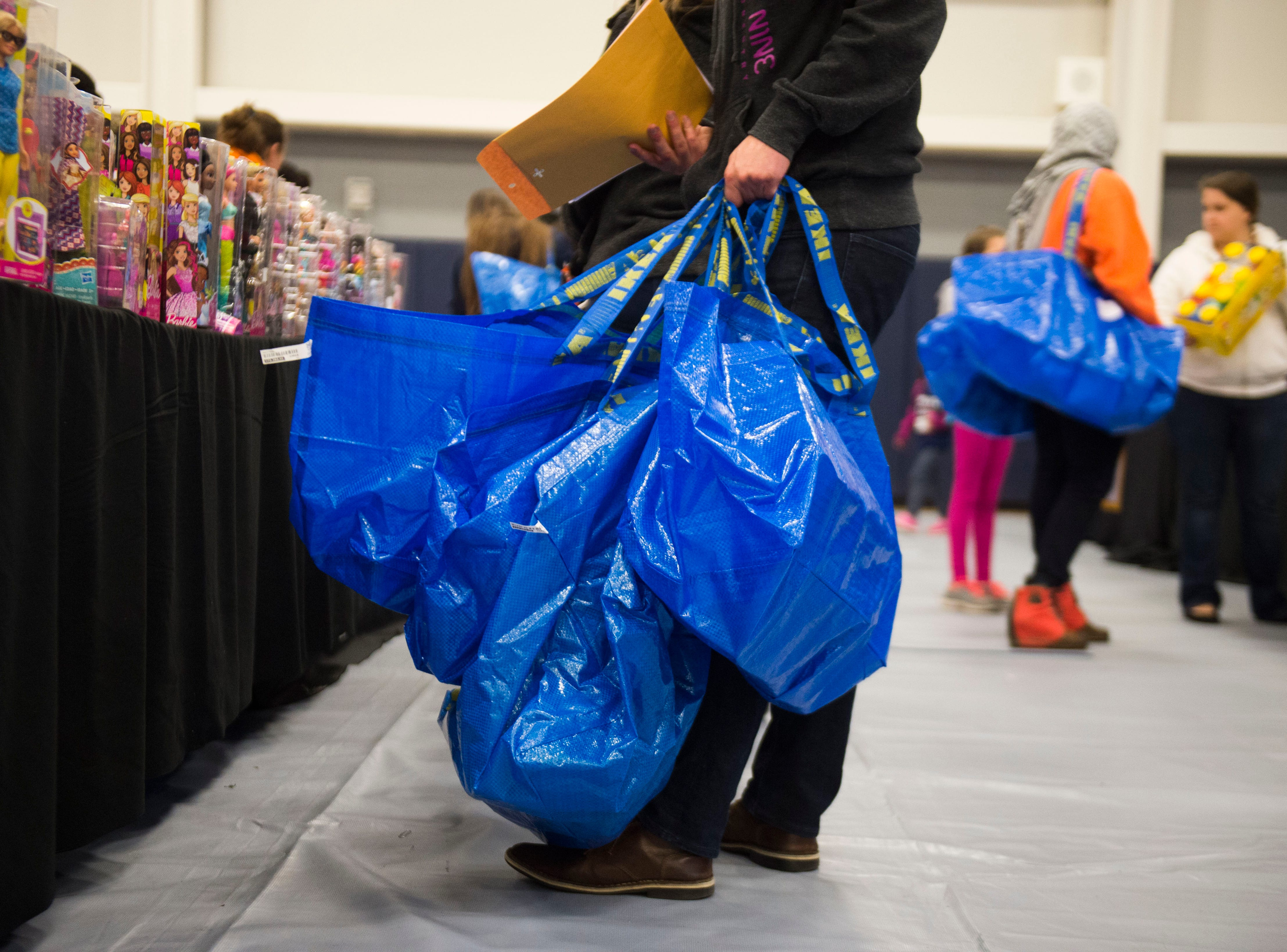 A person holds shopping bags at the Boys and Girls Clubs Regal Teen Center in Knoxville Saturday, Dec. 8, 2018. Parents, grandparents or guardians of over 1,500 underserved children were able to pick out a limited number of free gifts for their child.