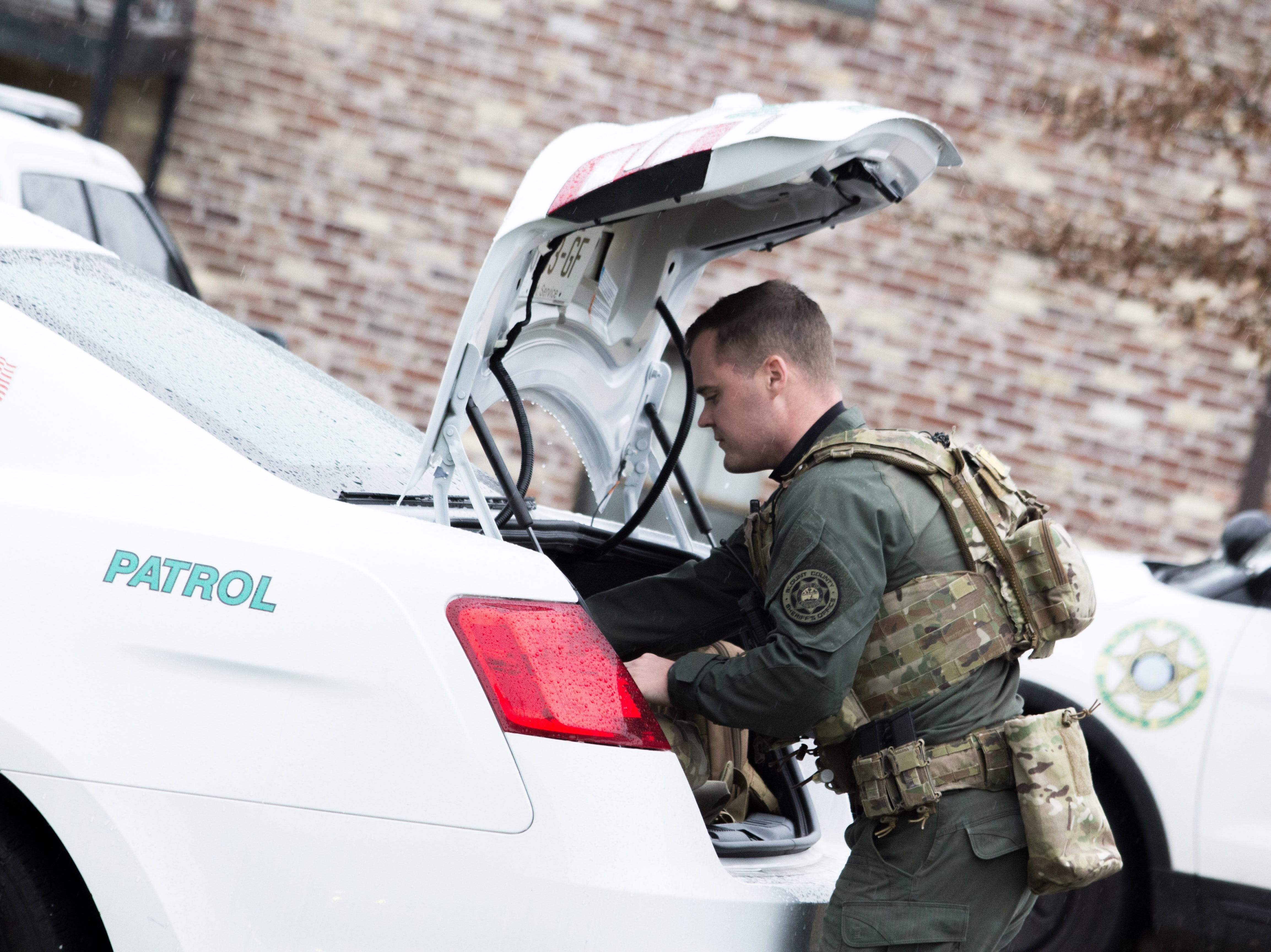 An officer grabs gear from the trunk of a patrol car during a standoff between the Blount County Sheriff's Office and a 21-year-old man. The man was killed during the standofffollowing shots from officers and a self-inflicted wound on Dec. 8, 2018.