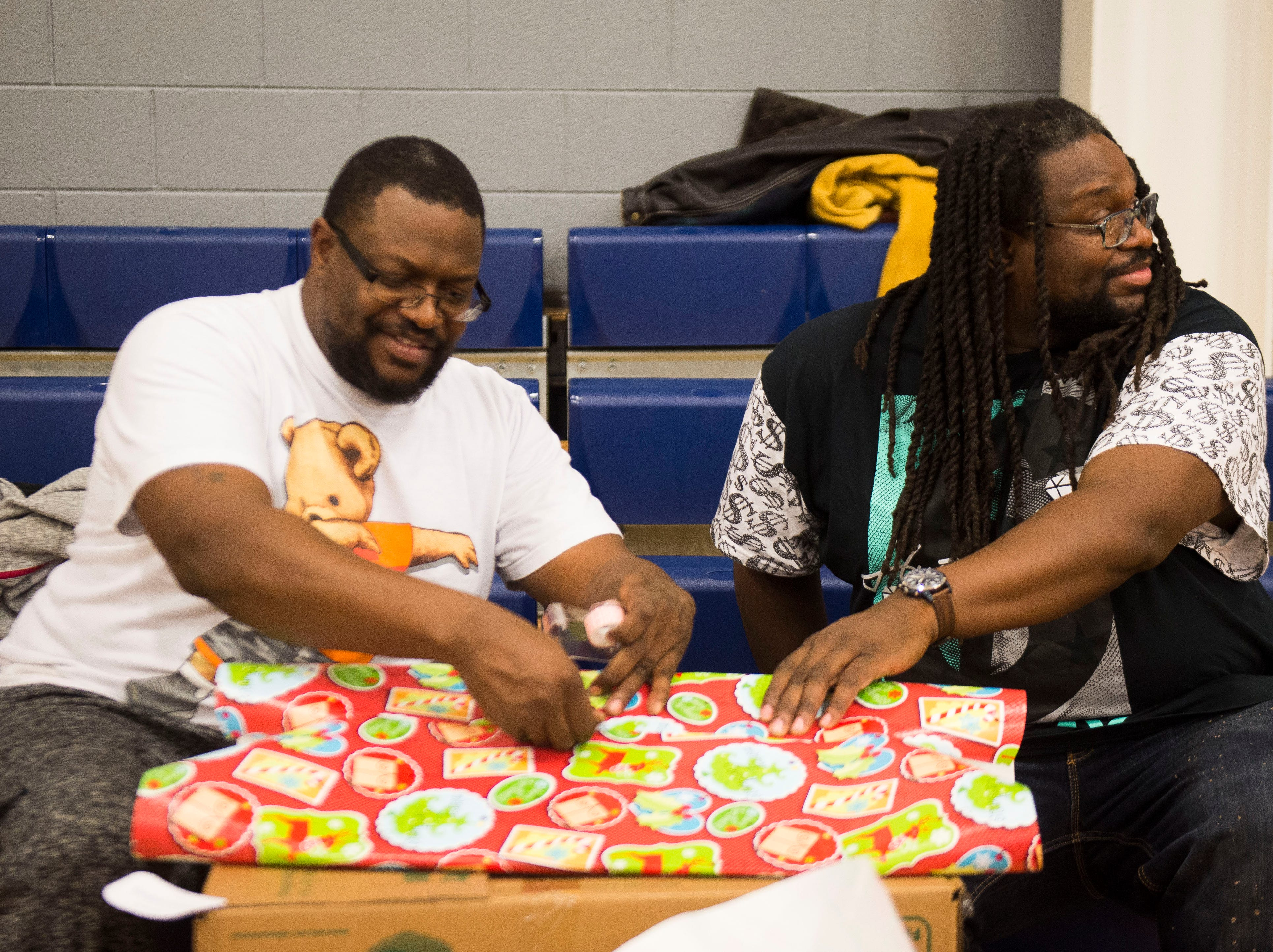 Maurice and Dion Chandler wrap presents at the Boys and Girls Clubs Regal Teen Center in Knoxville Saturday, Dec. 8, 2018. Parents, grandparents or guardians of over 1,500 underserved children were able to pick out a limited number of free gifts for their child.