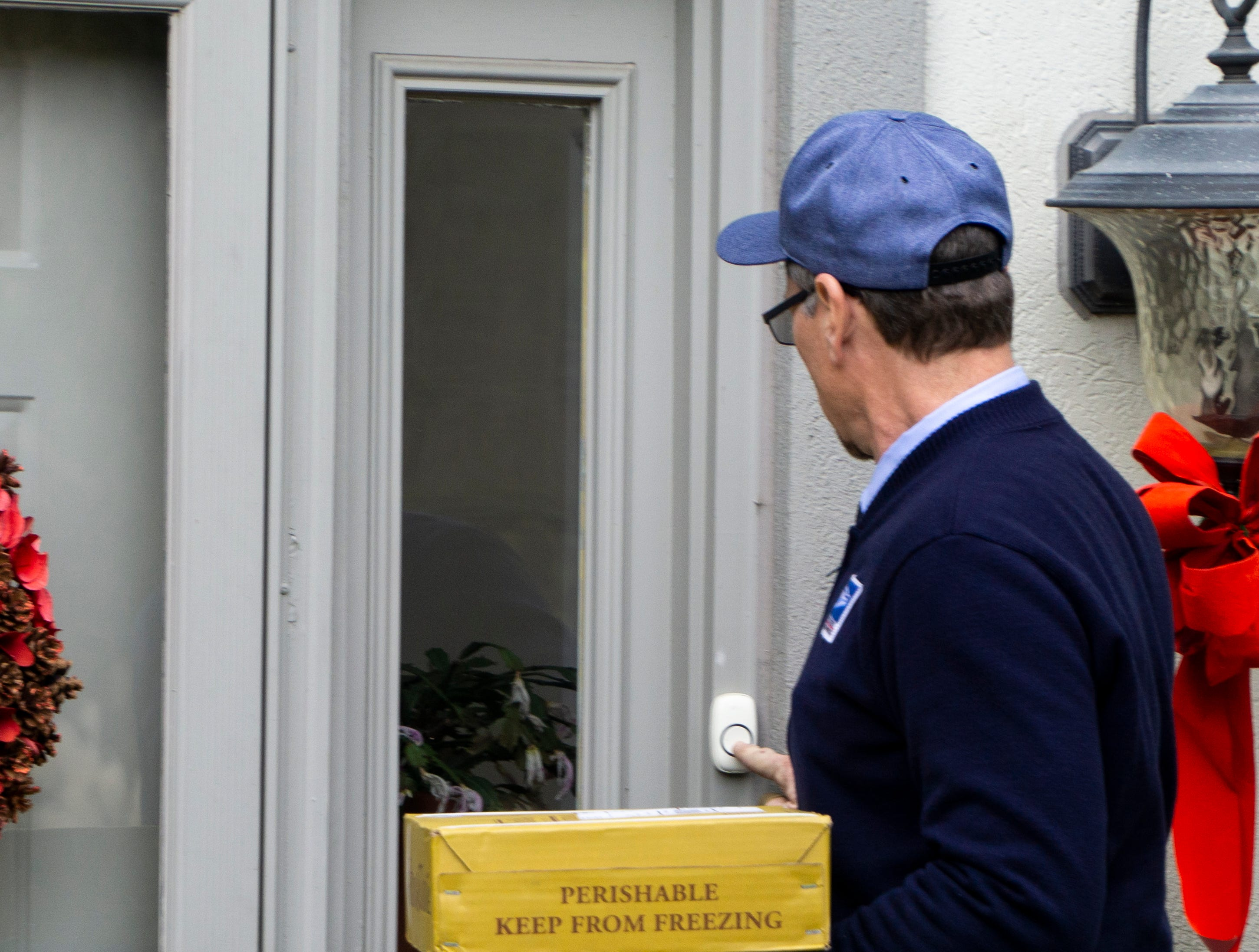 Bryan Lay delivers a package to a West Knoxville home on Friday, Dec. 7. USPS says it will deliver some 900 million packages this holiday season, which runs from Thanksgiving to New Year's Eve.