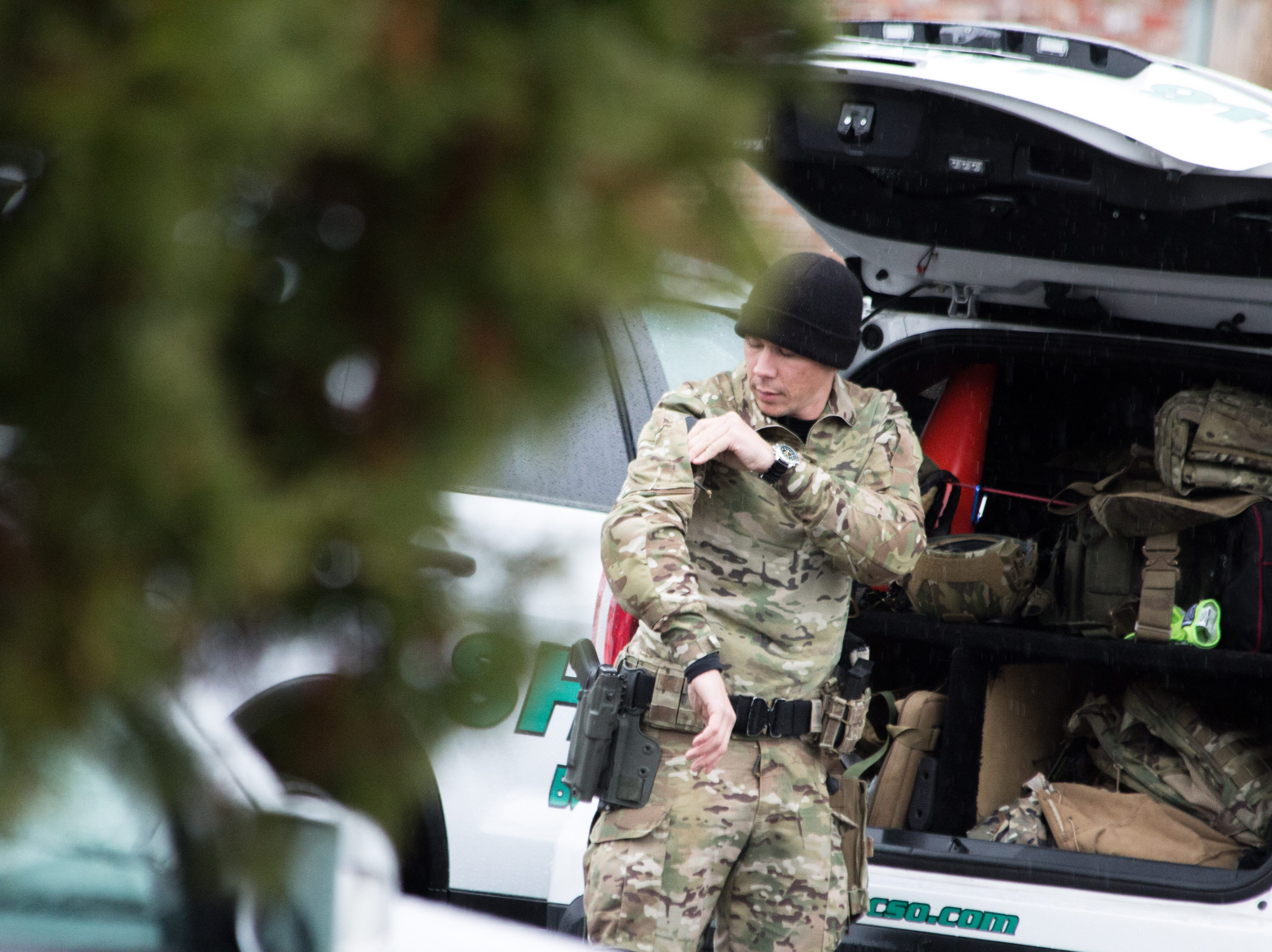 An officer adjusts his uniform before returning to the scene of a standoff that lasted roughly 8 hours at a Blount County apartment complex on Dec. 8, 2018. One man was killed.