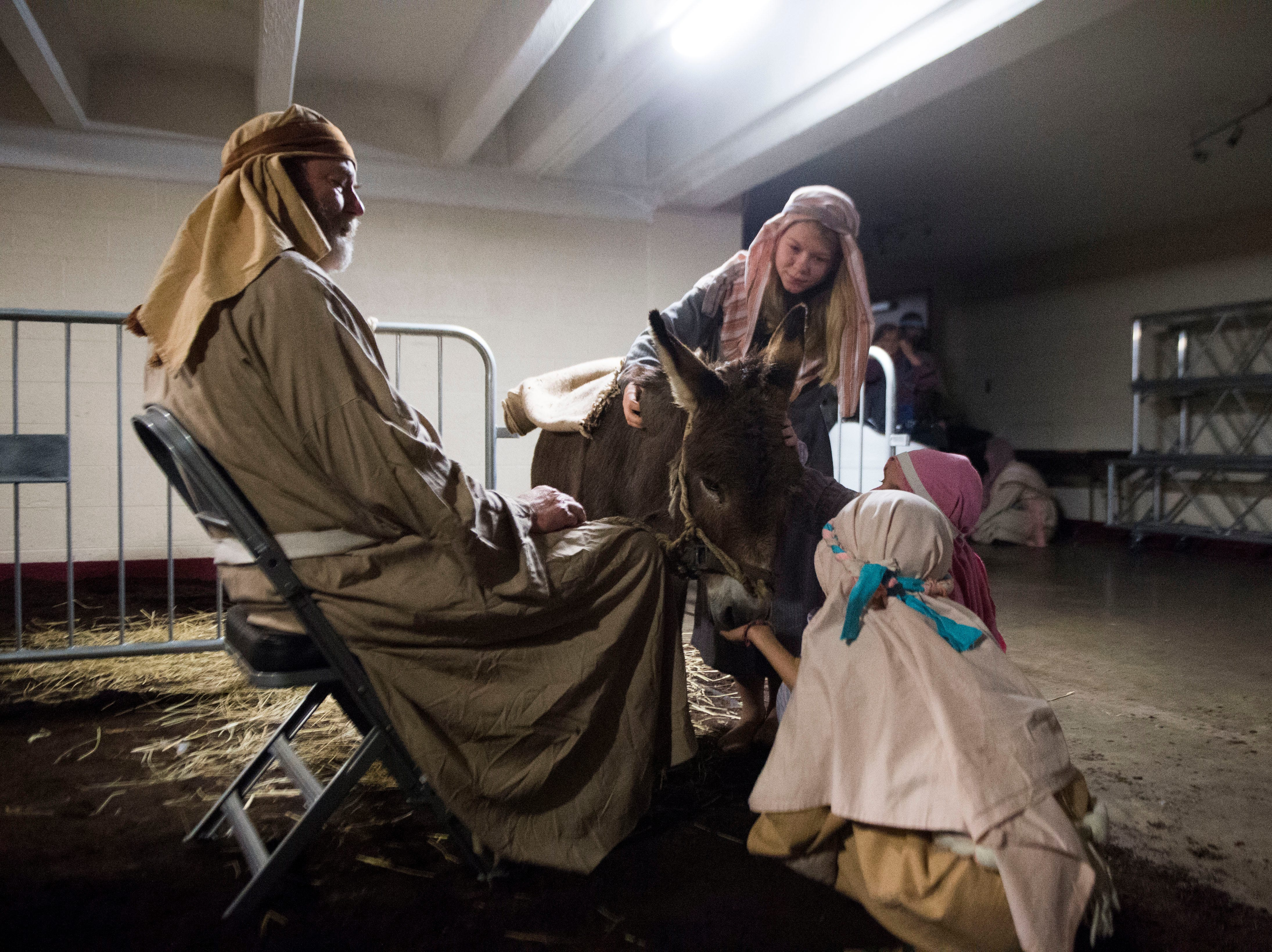 Actors pet an animal backstage at he annual Knoxville Nativity Pageant at the Civic Coliseum Saturday, Dec. 8, 2018.