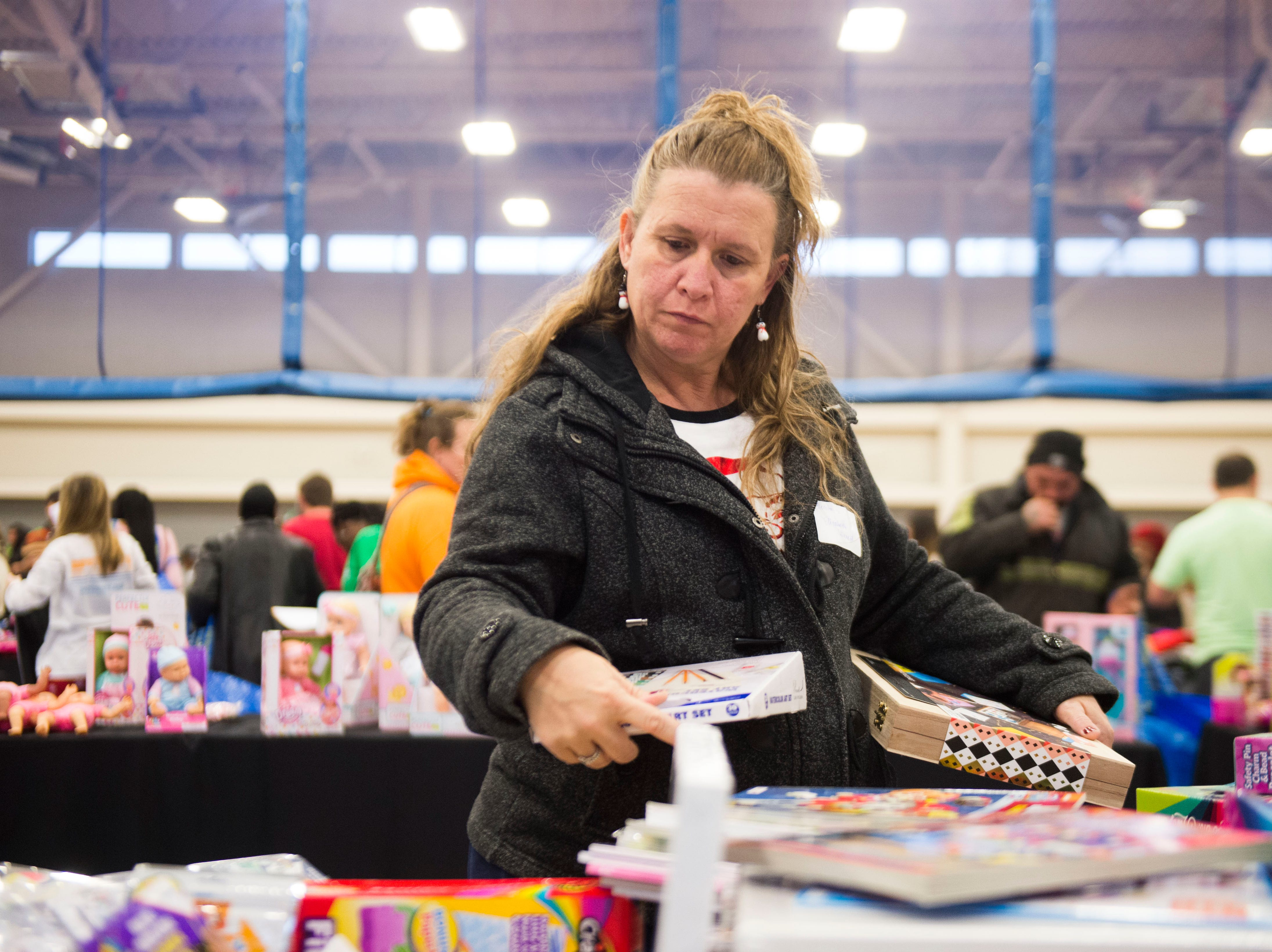 Elizabeth Stinnett checks out gifts at the Boys and Girls Clubs Regal Teen Center in Knoxville Saturday, Dec. 8, 2018. Parents, grandparents or guardians of over 1,500 underserved children were able to pick out a limited number of free gifts for their child.