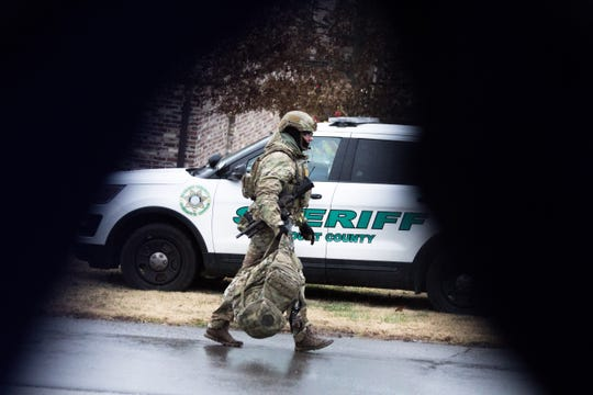 A member of the Blount County SWAT team walks toward the scene of a standoff just before officers fired shots at a man who came out with a gun. The man then shot himself and died on Saturday.