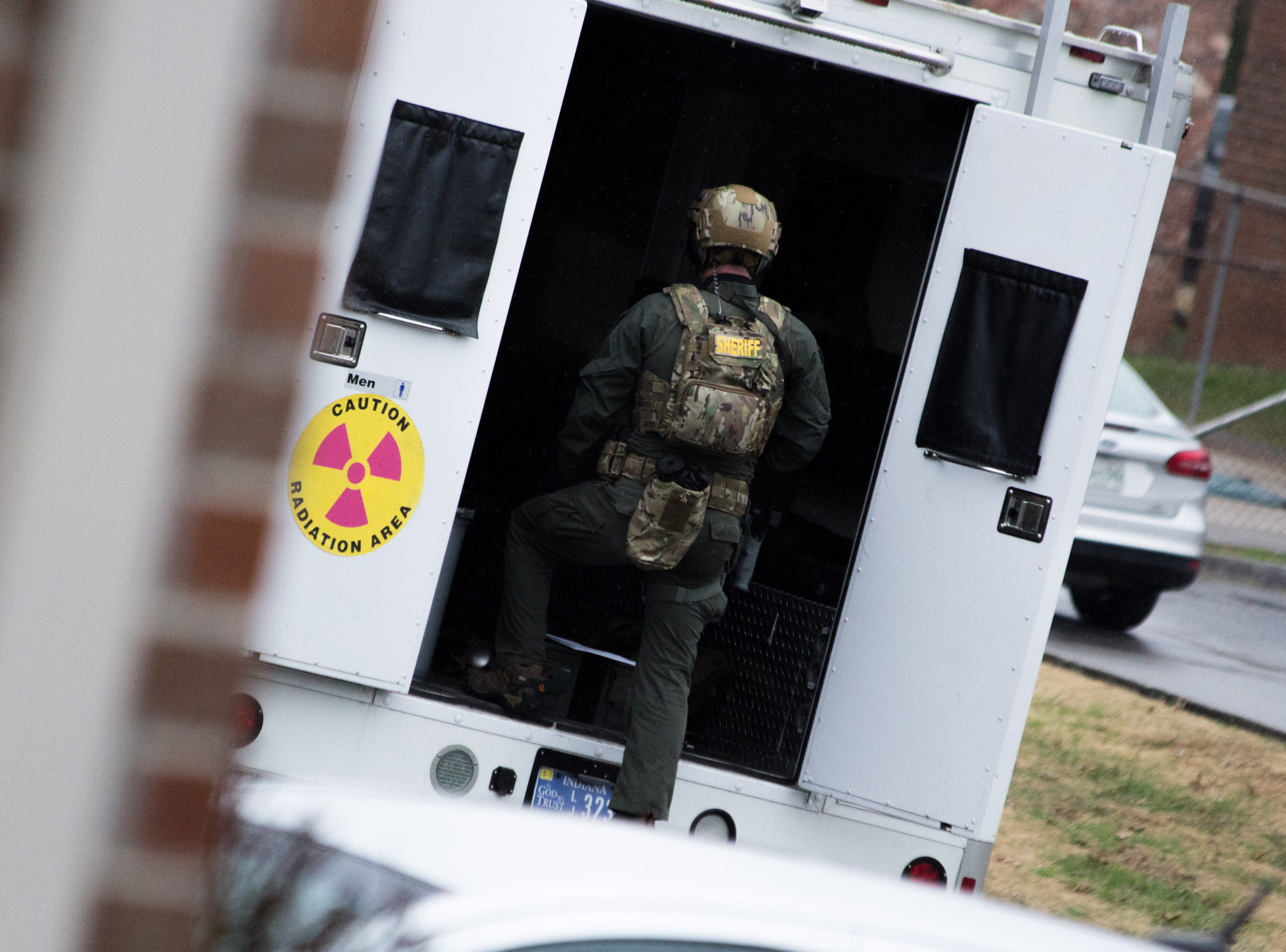 A Blount County officer returns to a vehicle during an hours-long standoff at a Blount County apartment complex on Dec. 8, 2018. One man was killed.