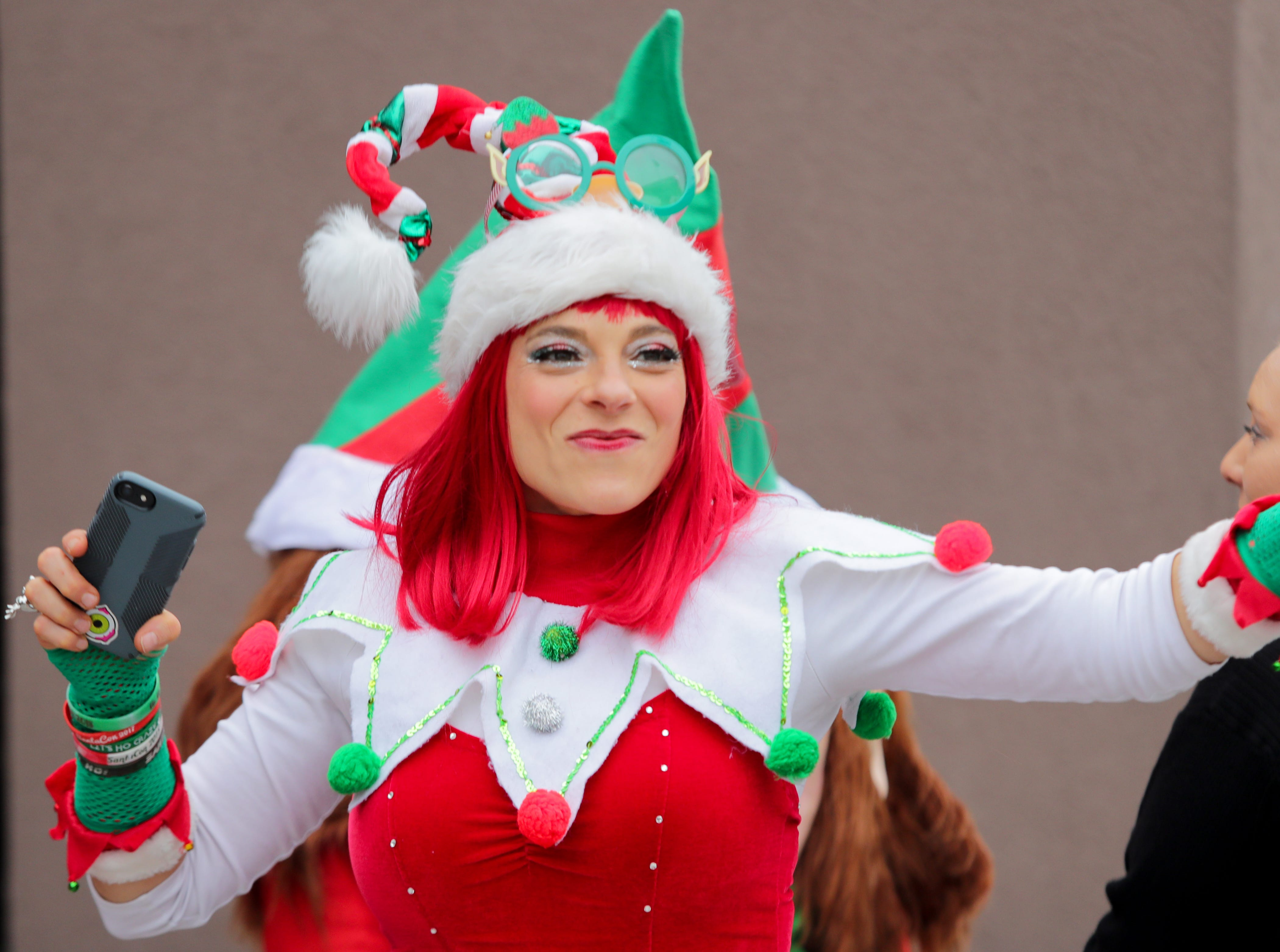 Jenna Ankenbrand, one of Santa's workers, pumps up the crowd at 8UP, SantaCon's first location of the day,    Dec. 8, 2018