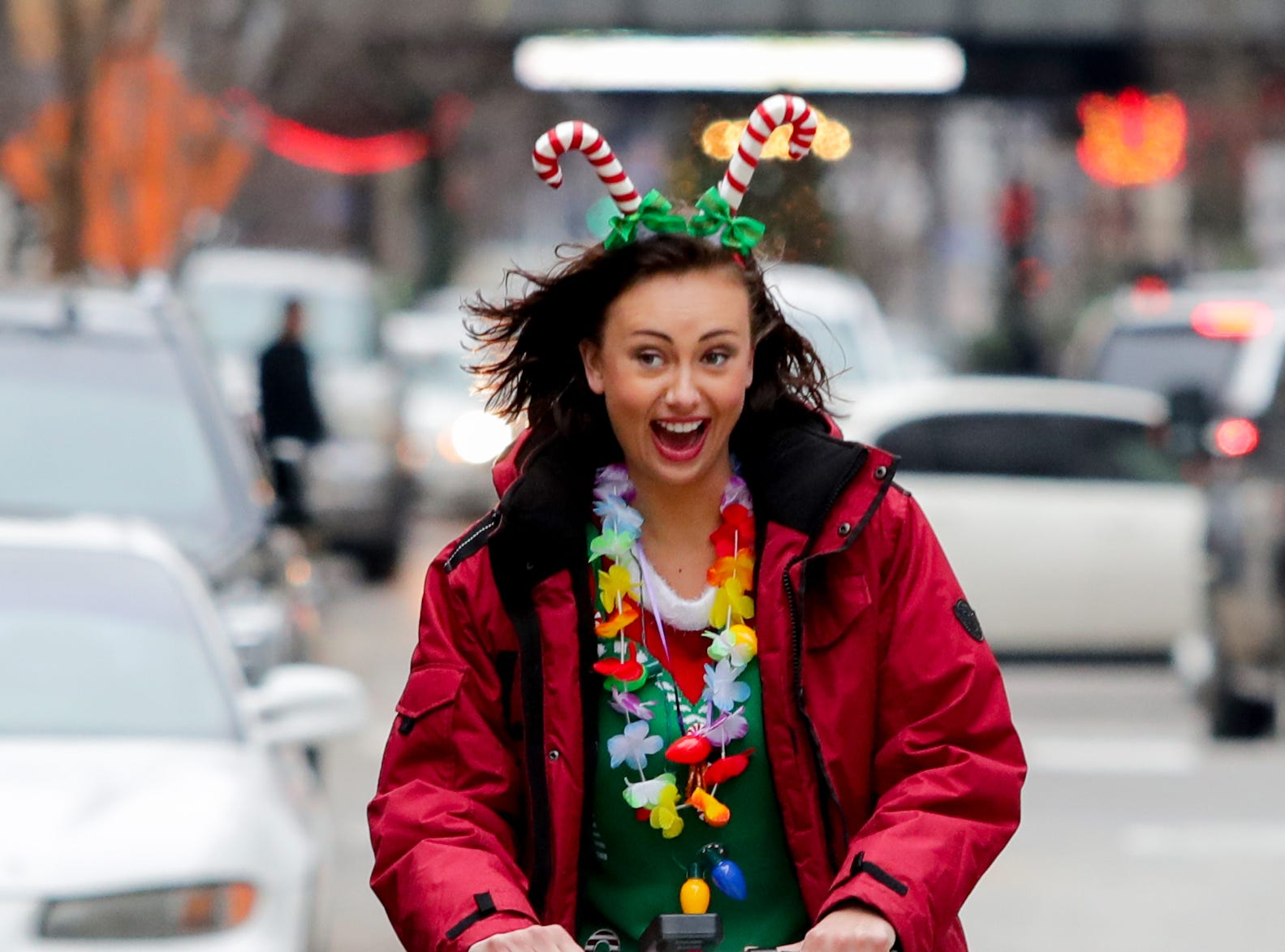 Kelcie Perez uses a Bird to get from one location to another on the SantaCon journey. Dec. 8, 2018