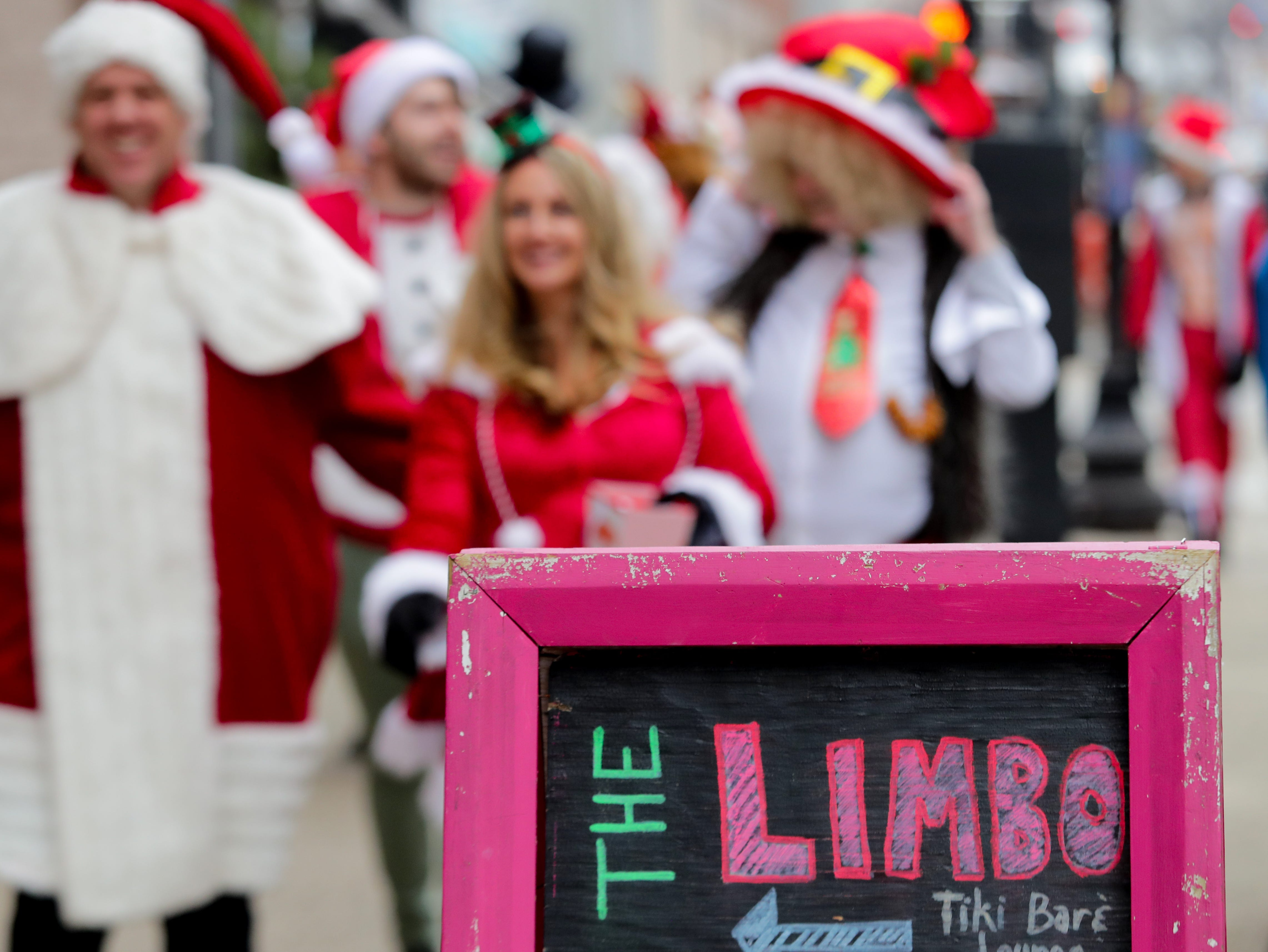 The crowd enjoys The Limbo, the second location on the Louisville SantaCon journey. Dec. 8, 2018