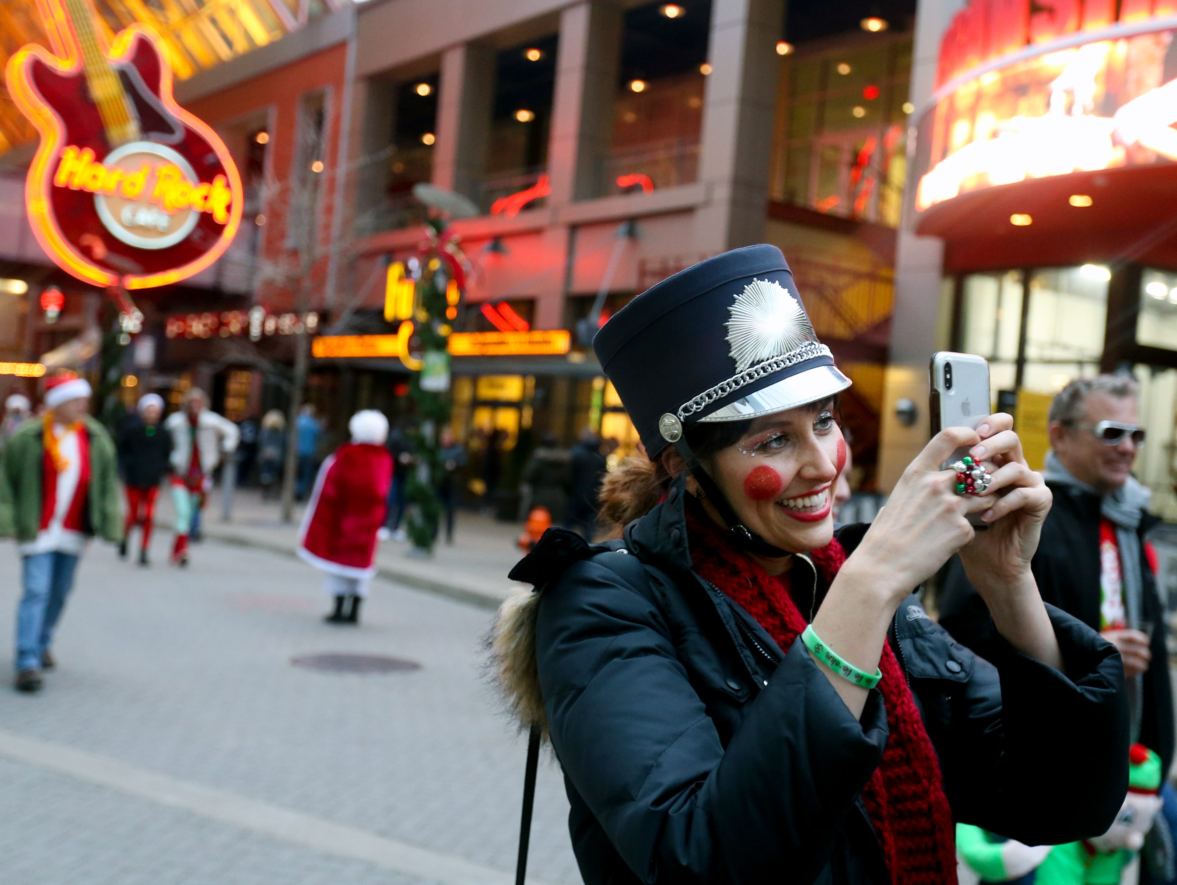 Marge Royston takes a photo in-between stops at Louisville's SantaCon.Dec. 8, 2018